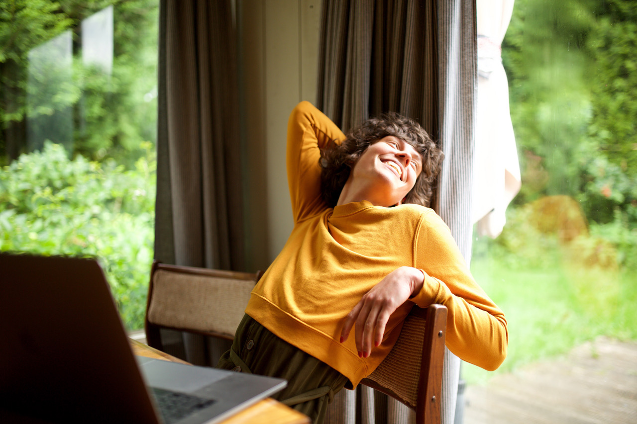 Portrait of woman relaxing at home looking out of window