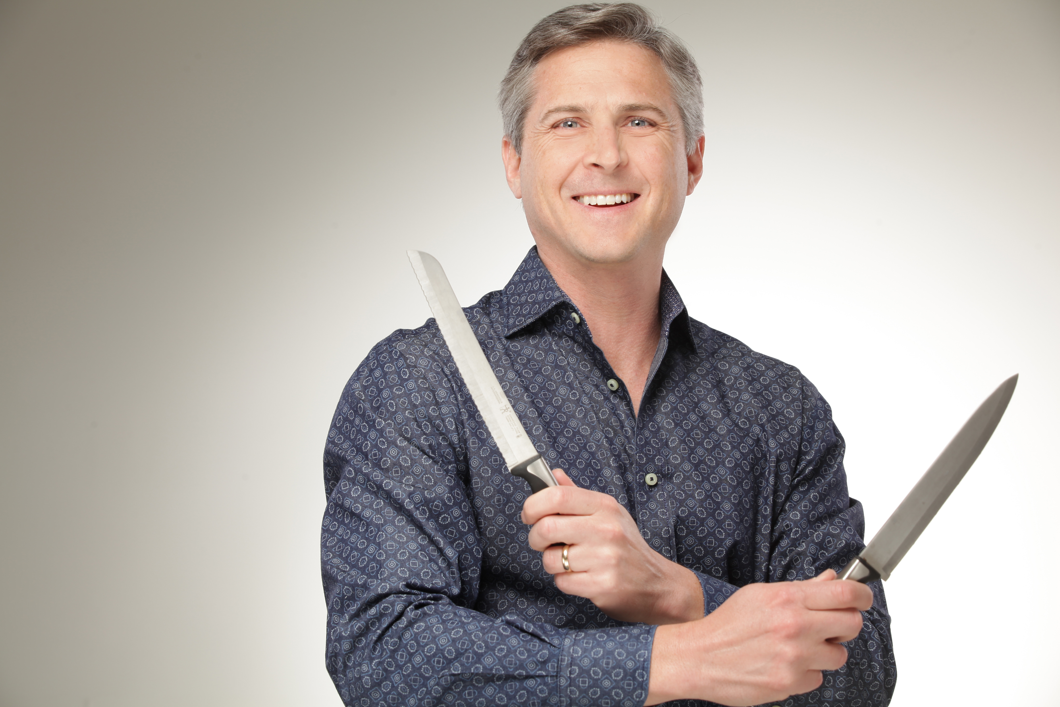 "Dr. Blake Shusterman, aka ""The Cooking Doc"" holds two steak knives"