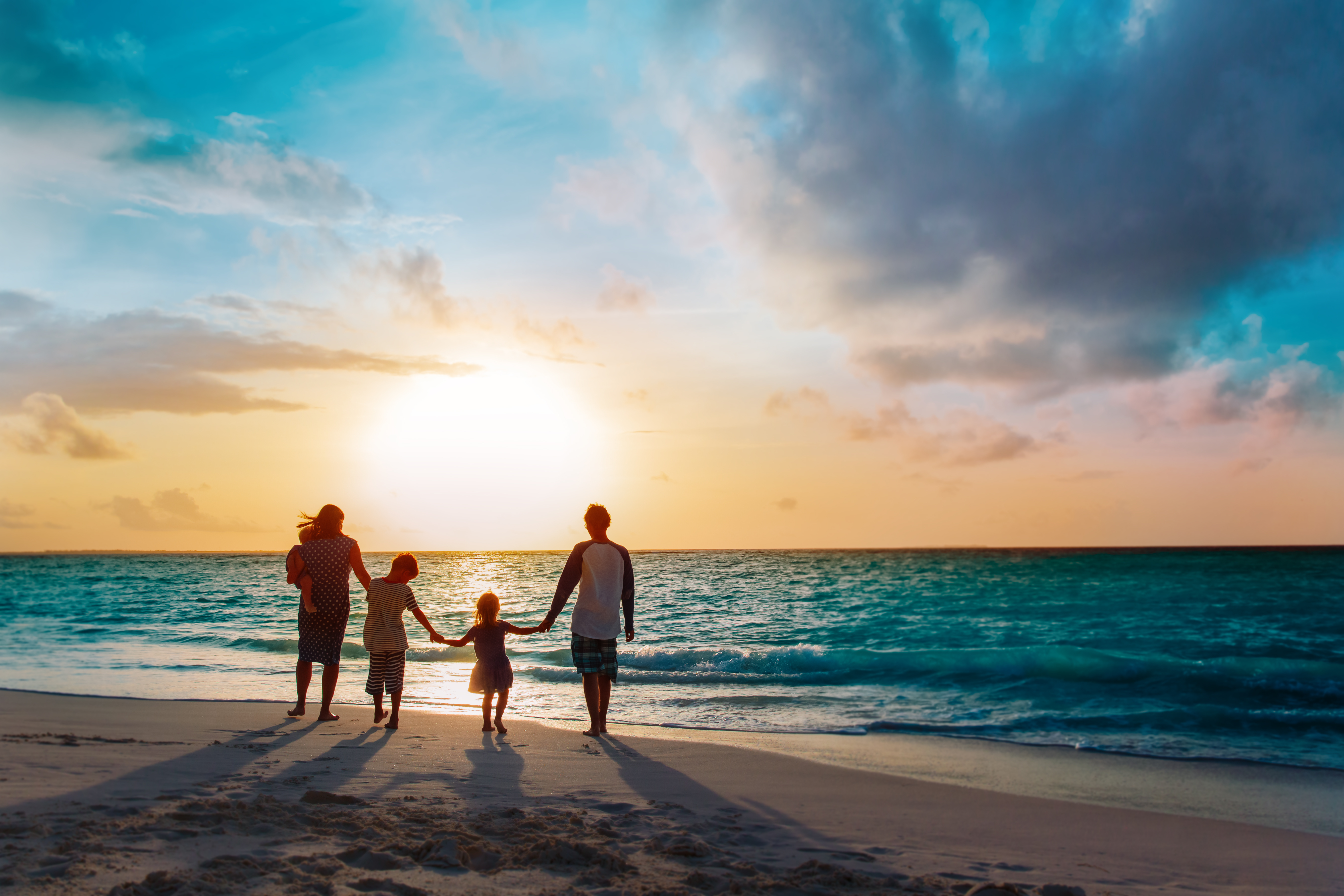 happy family with tree kids walk at sunset tropical beach