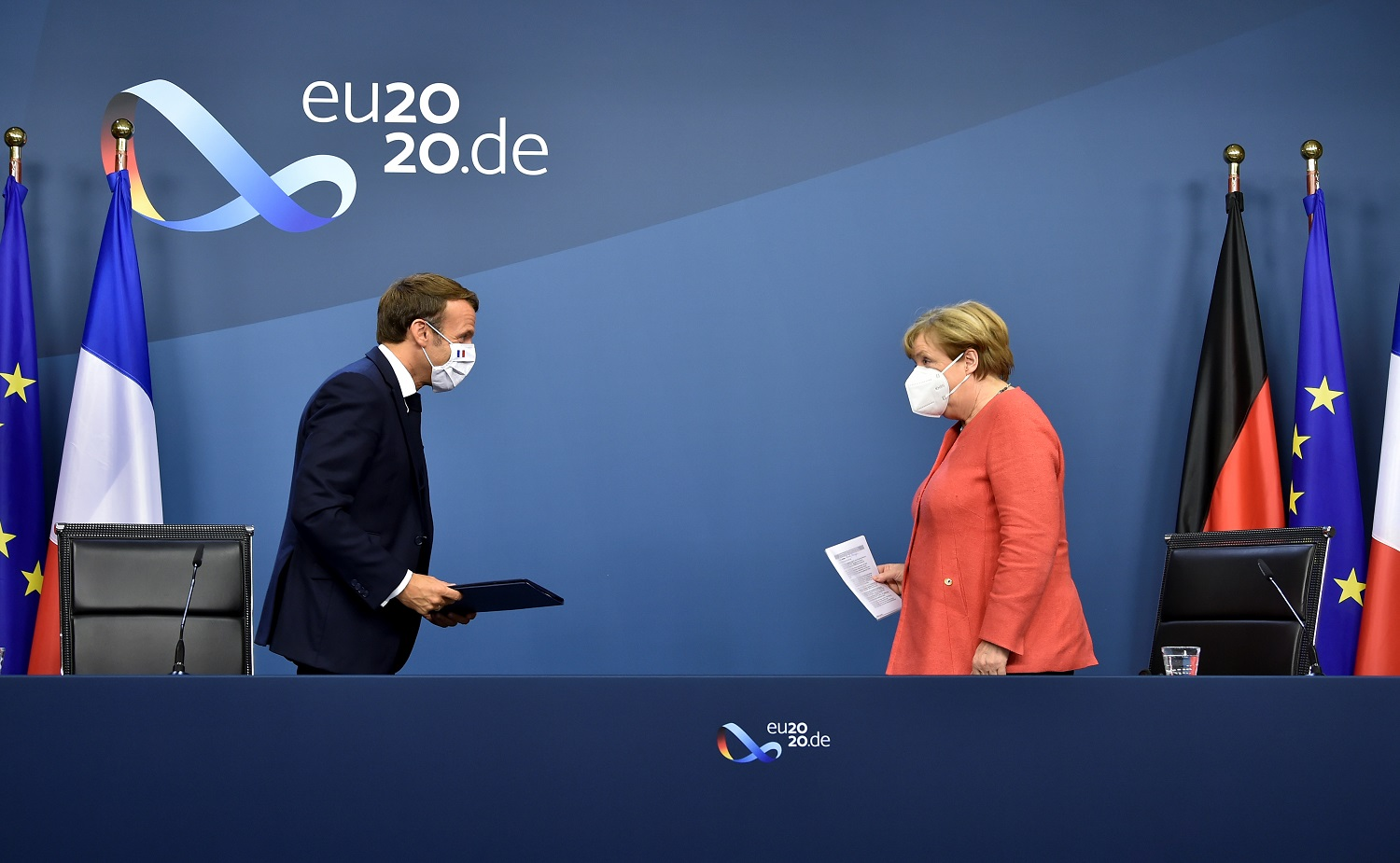 German Chancellor Angela Merkel and French President Emmanuel Macron leave after their joint video press conference at the end of the European summit at the EU headquarters in Brussels, Belgium July 21, 2020. John Thys/Pool via REUTERS