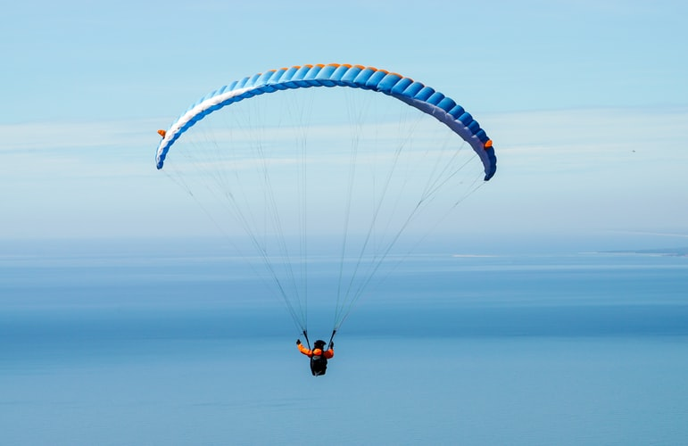 A paraglider in the middle of the blue sky