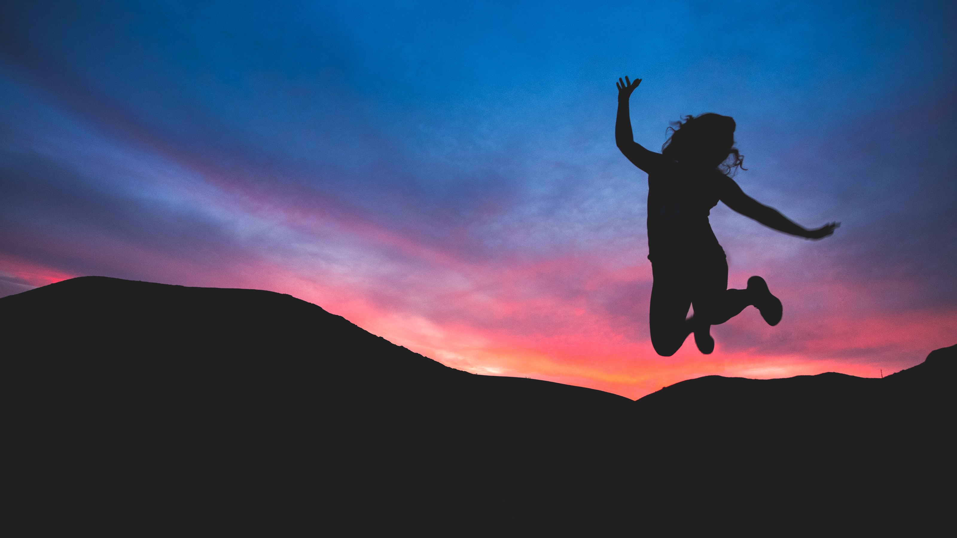 Happy woman jumping by a sunset