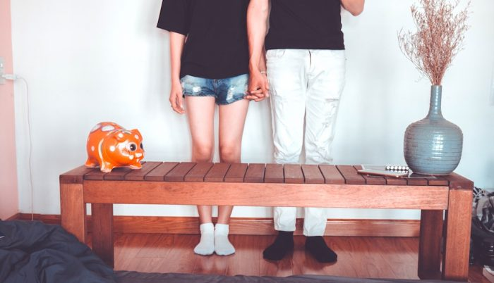 A young couple holding hands and standing in front of a bench at home