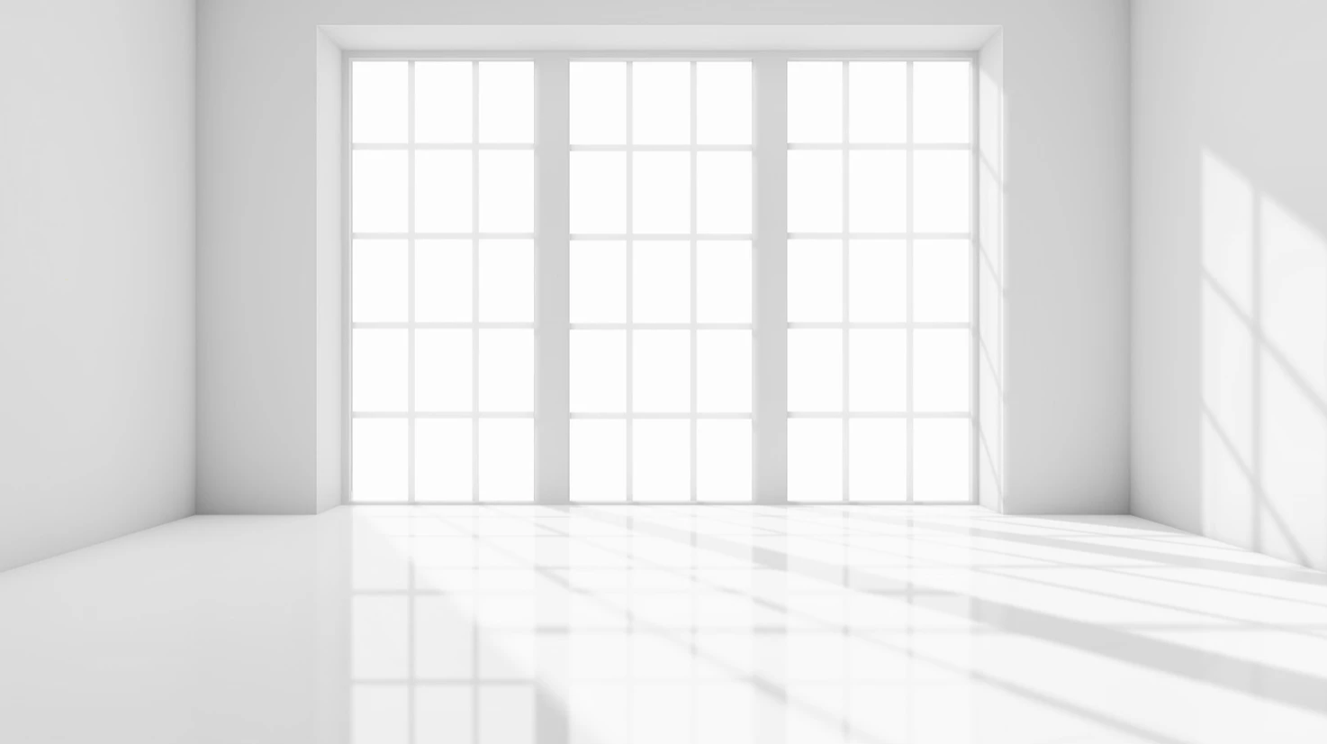 An empty room with bare floor to ceiling windows, shining light into the room.