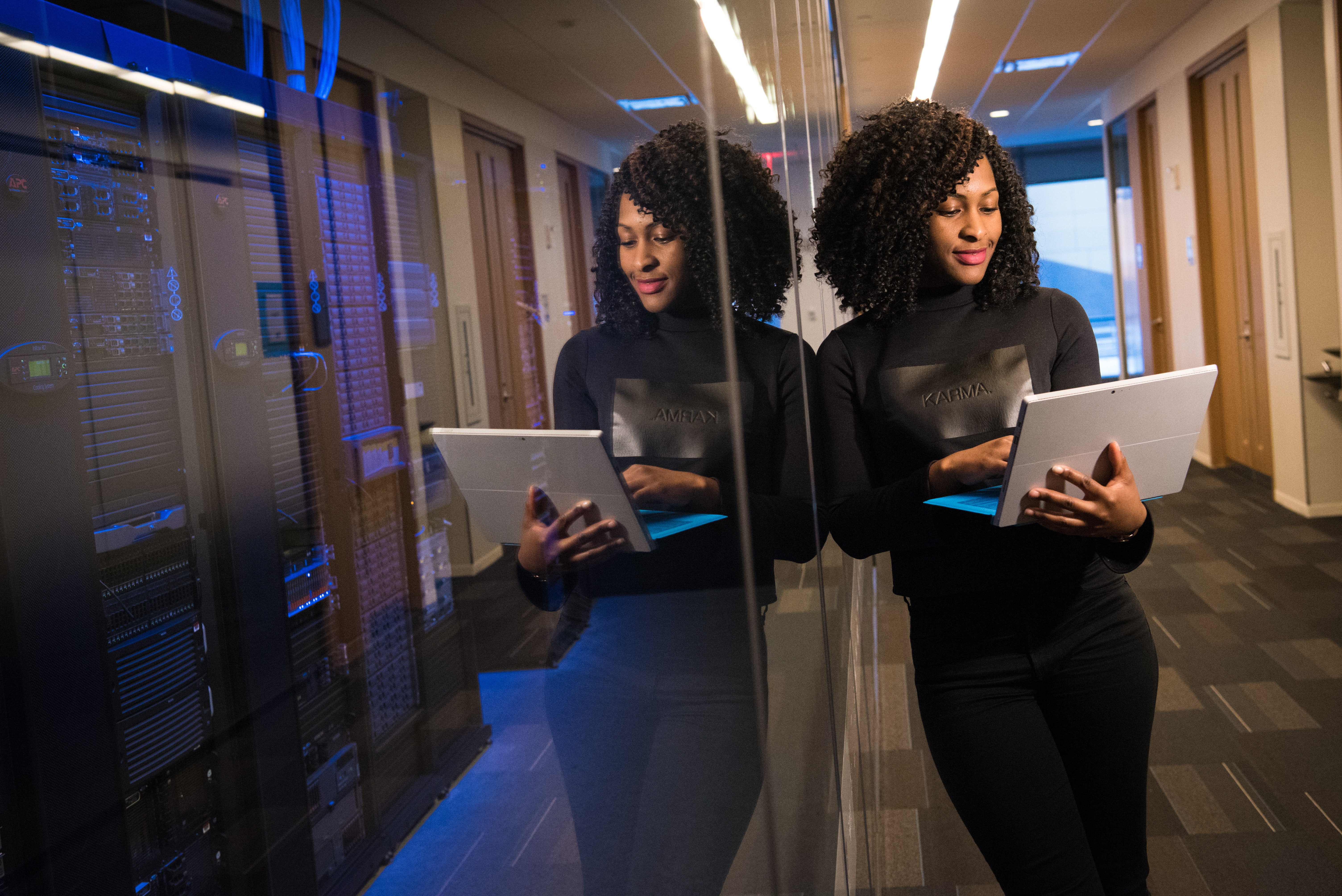 African-American woman holding laptop and leaning against glass wall in office