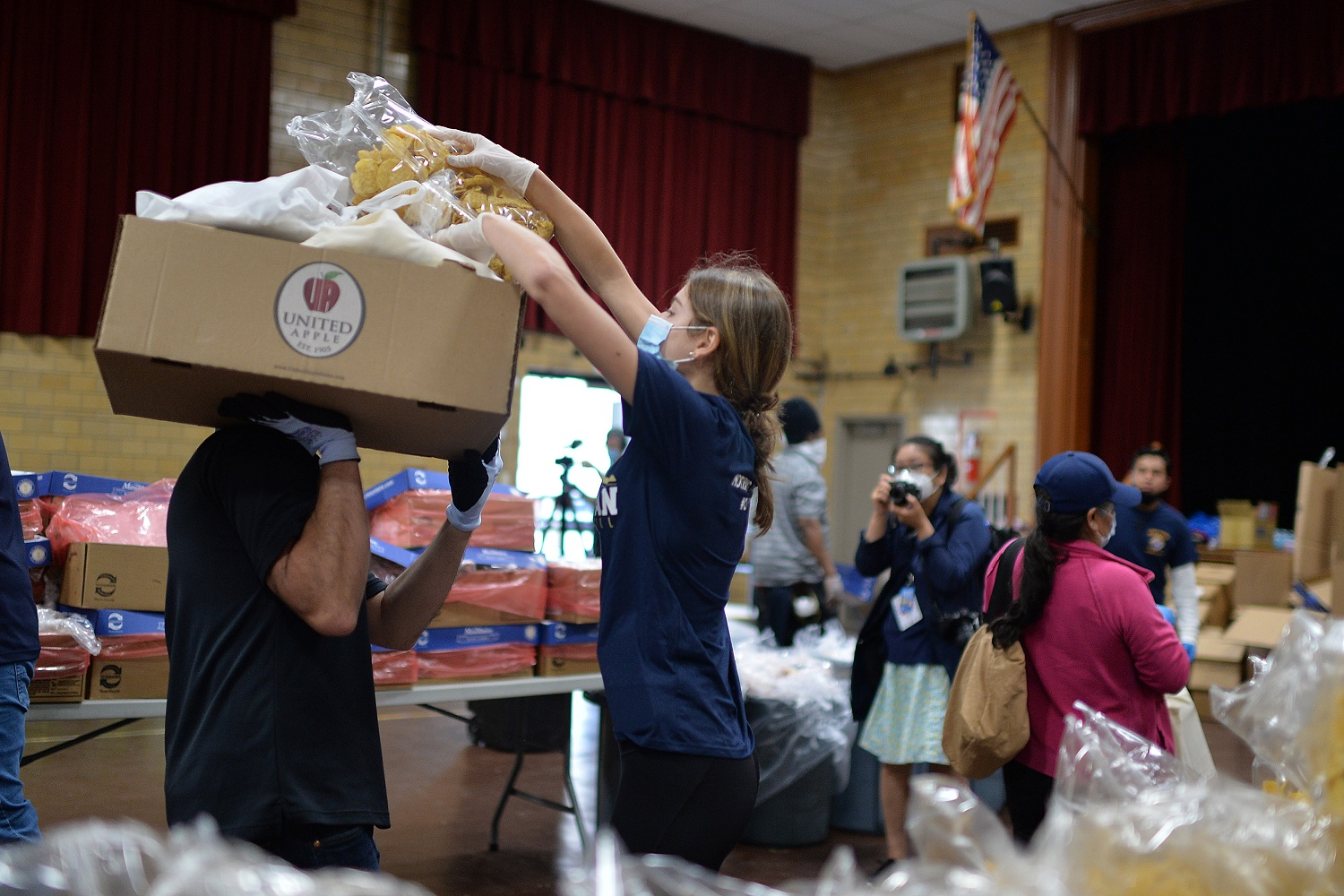 Wearing protective masks and gloves in the time of COVID-19, volunteers help prepare and distribute donated food to people seeking assistance at St. Finbar Catholic Church, in the Brooklyn borough of New York, NY, May 29, 2020. With enough food packages for 1500 individuals, Catholic Charities Brooklyn and Queens distributed food to those suffering from food insecurities caused by the impact of the Coronavirus pandemic and Its effect on the economy. (Anthony Behar/Sipa USA)No Use UK. No Use Germany.