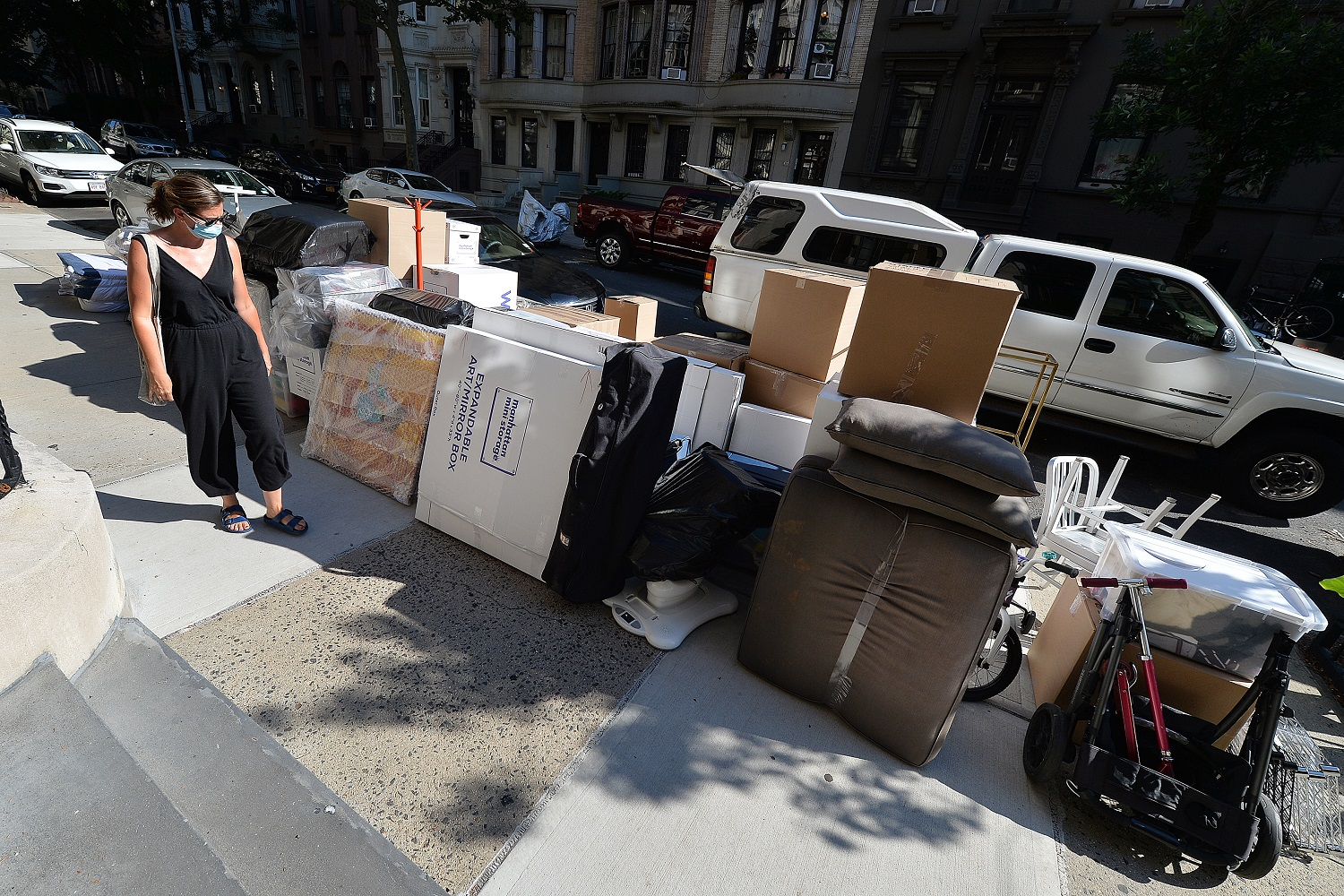 "A woman wearing a mask in the time of COVID-19, walks past Moving boxes stacked in front of an Upper West Side brownstone, waiting for movers to finish packing the belongings of former tenants that have already relocated out of state, New York, NY, July 13, 2020. Complicated by the economic impact of the COVID-19 pandemic, months of ""shelter in place"", daily protests, social clashes and and the slow reopening of the economy, have forced many New Yorkers to leave a city where rents are high and future job opportunities are difficult to predict. (Anthony Behar/Sipa USA)No Use UK. No Use Germany."