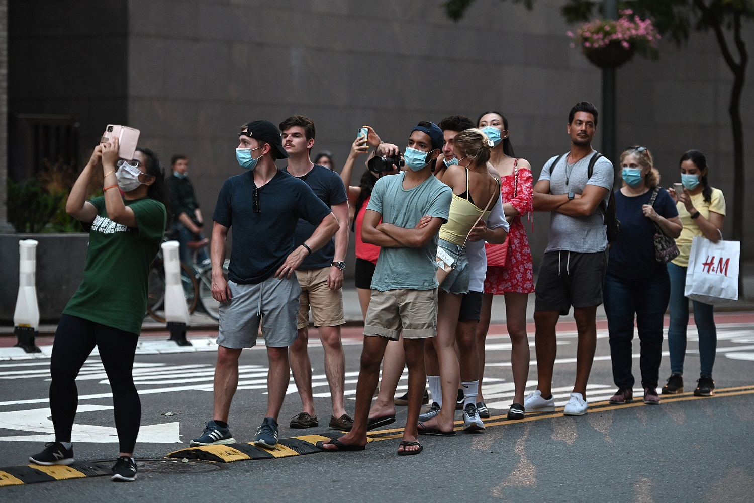 """Some wearing face masks in the time of COVID-19, people line up along the median strip along 42nd Street and Second Avenue waiting for the sunset phenomenon known as """"Manhattanhenge"""", which was not viewable from that location for a second night in a row due to lingering storm clouds on the horizon, New York, NY, July 12, 2020. Manhattanhenge is the event during which the setting (or rising) sun aligns perfectly with east-west streets of the Manhattan island street grid, which occurs twice a year. (Anthony Behar/Sipa USA)No Use UK. No Use Germany."""