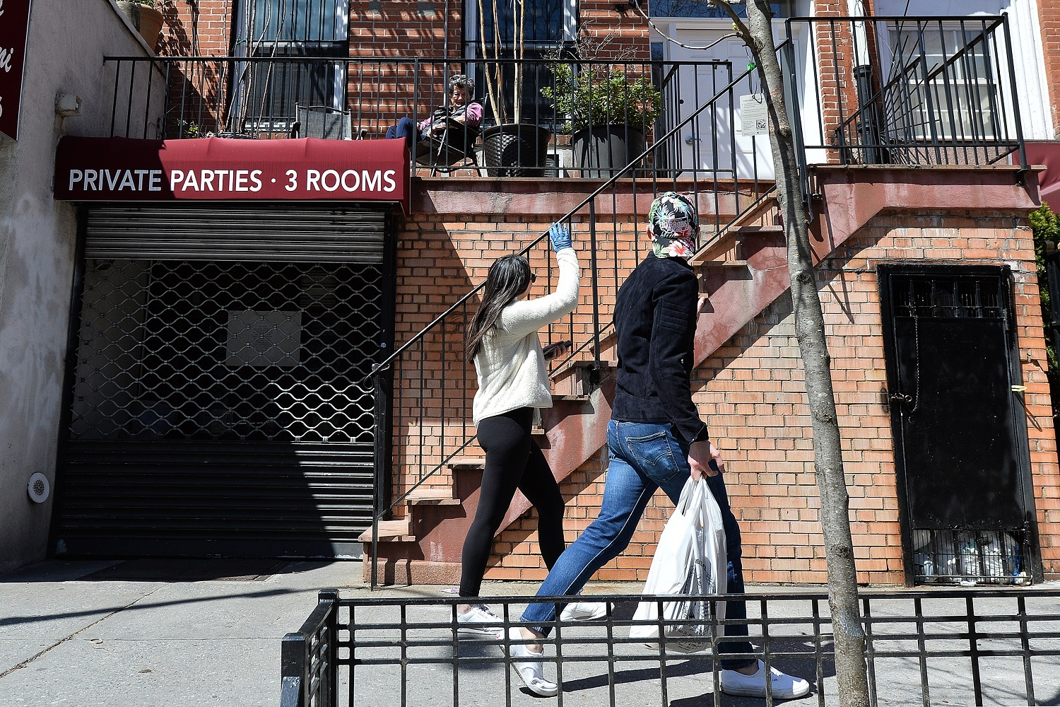 """As an act of kindness, a woman who only wants to be known as """"Jaon"""" waves and greets passersby from her second floor landing in the West Village section of New York City, NY, April 11, 2020. New York Gov. Andrew Cuomo announced that the number of positive Coronavirus cases, ICU admissions and hospitalizations are down indicating that New York may have reached the apex of the pandemic. (Anthony Behar/Sipa USA)No Use UK. No Use Germany."""