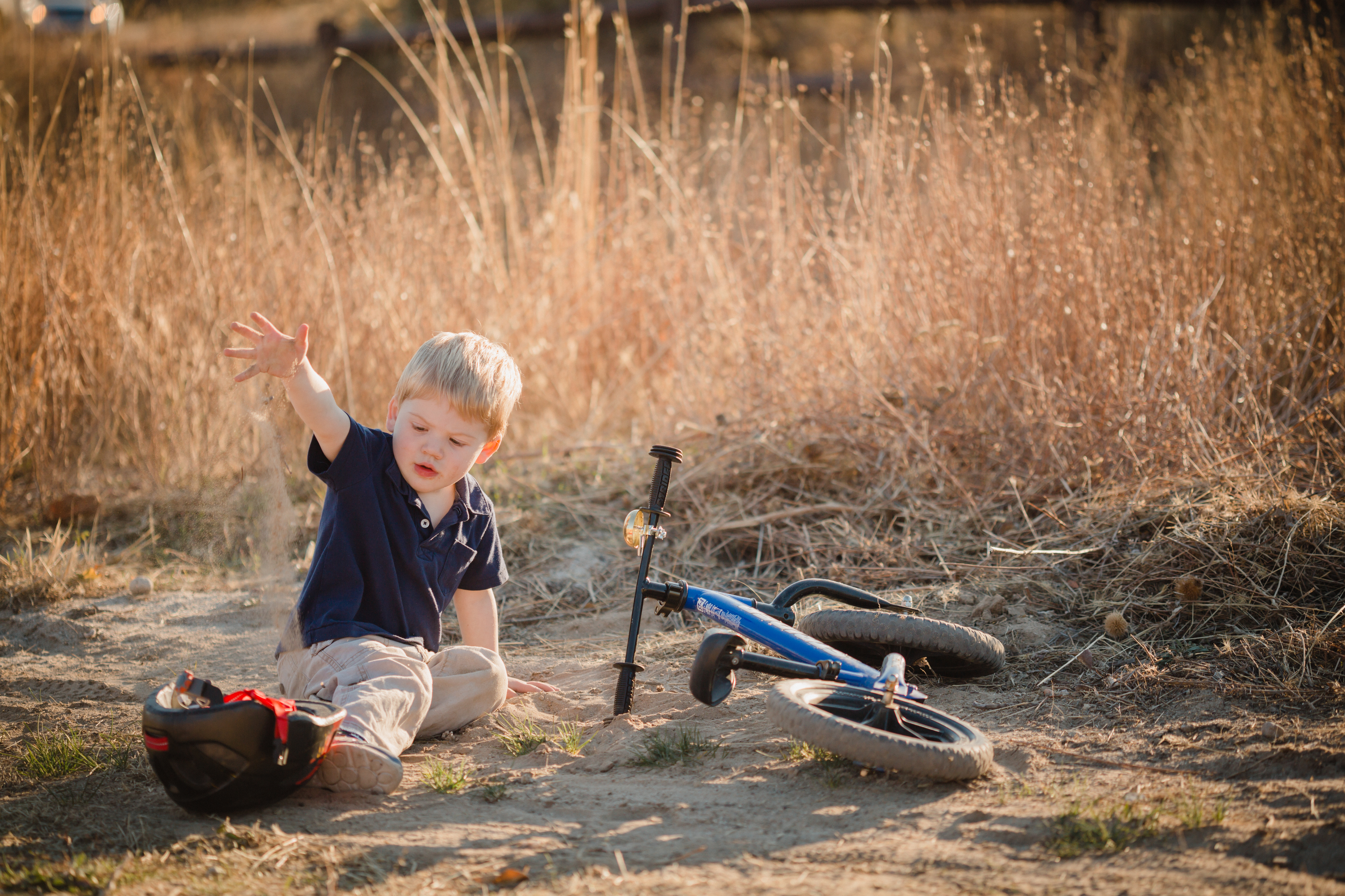 boy playing in dirt next to bike