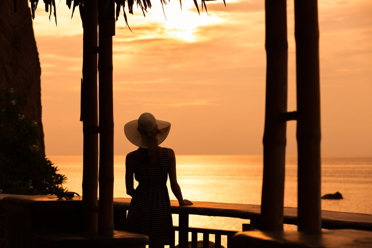 Woman enjoying beautiful sunset from the hotel balcony. Travel concept.