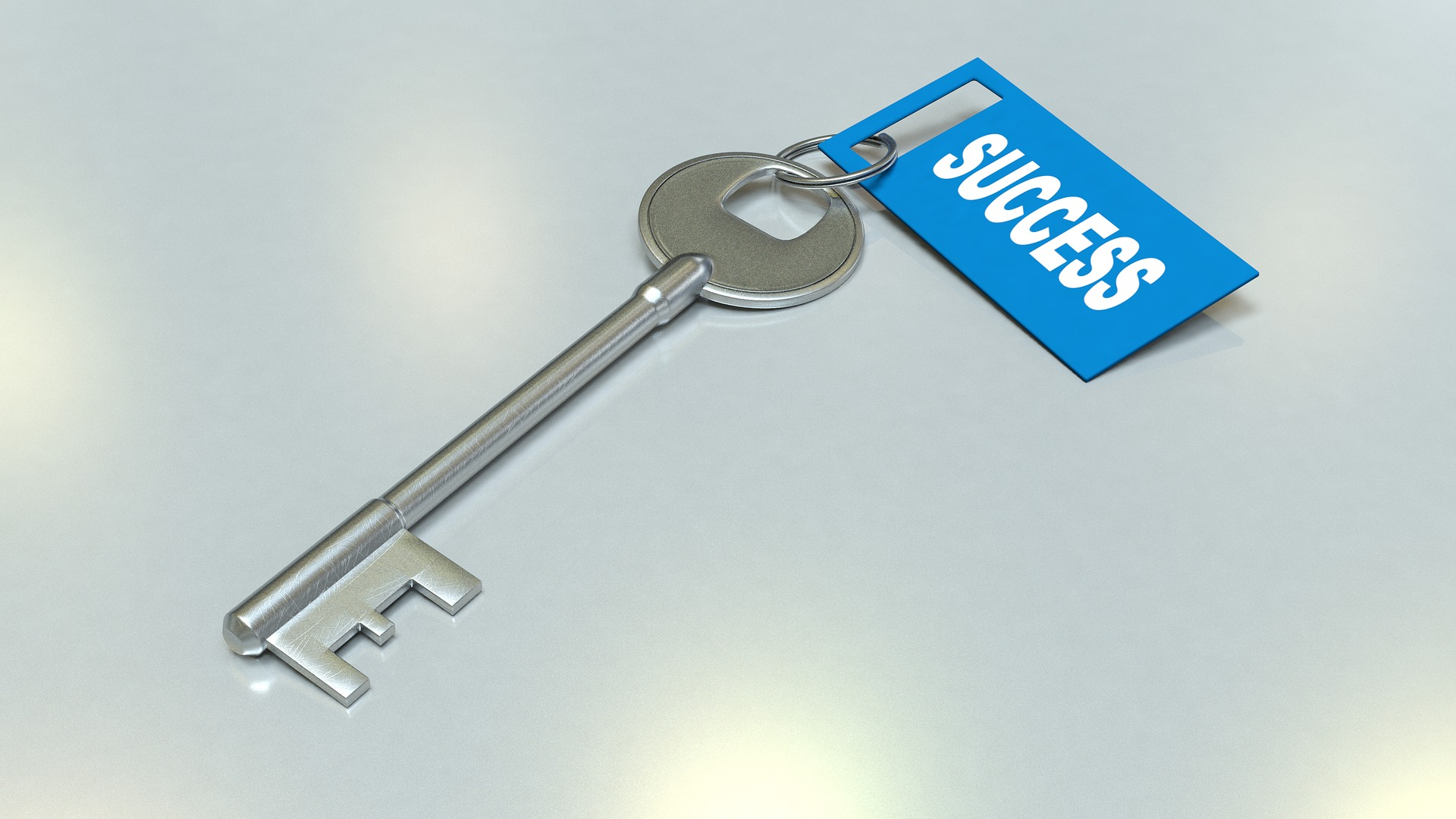 """A silver key with a tag saying """"Success"""""""