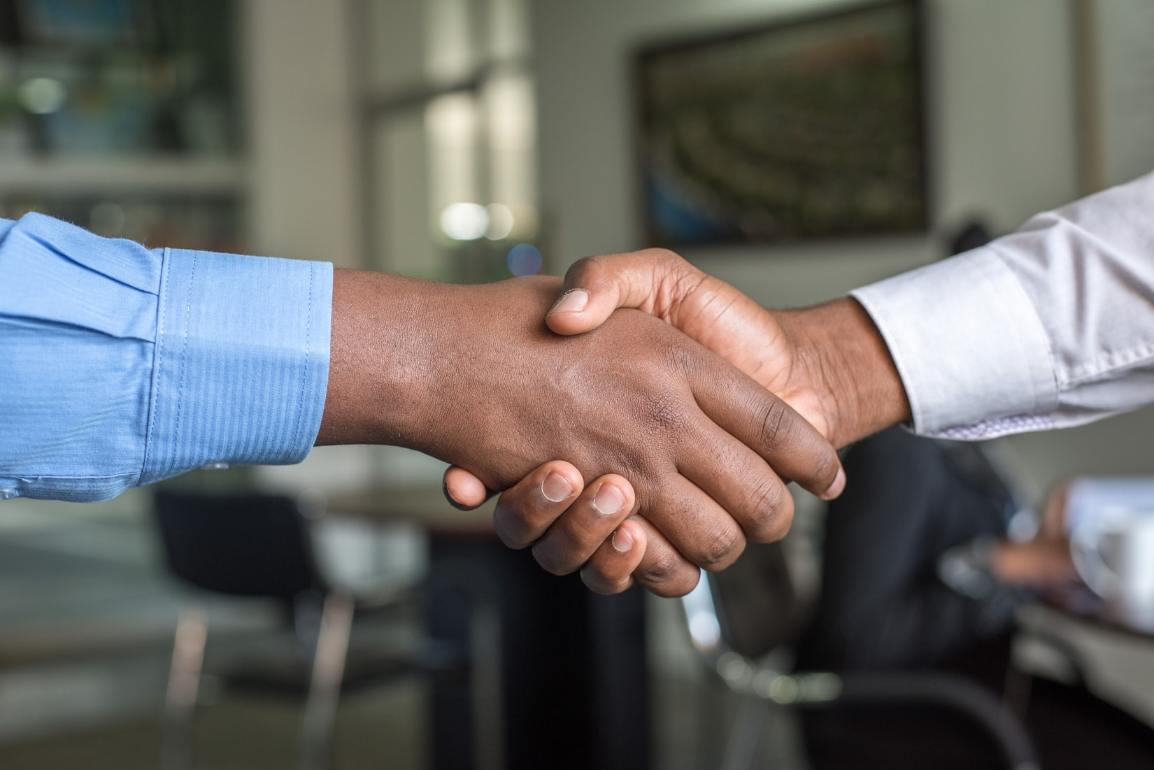 Two people of different races shaking hands