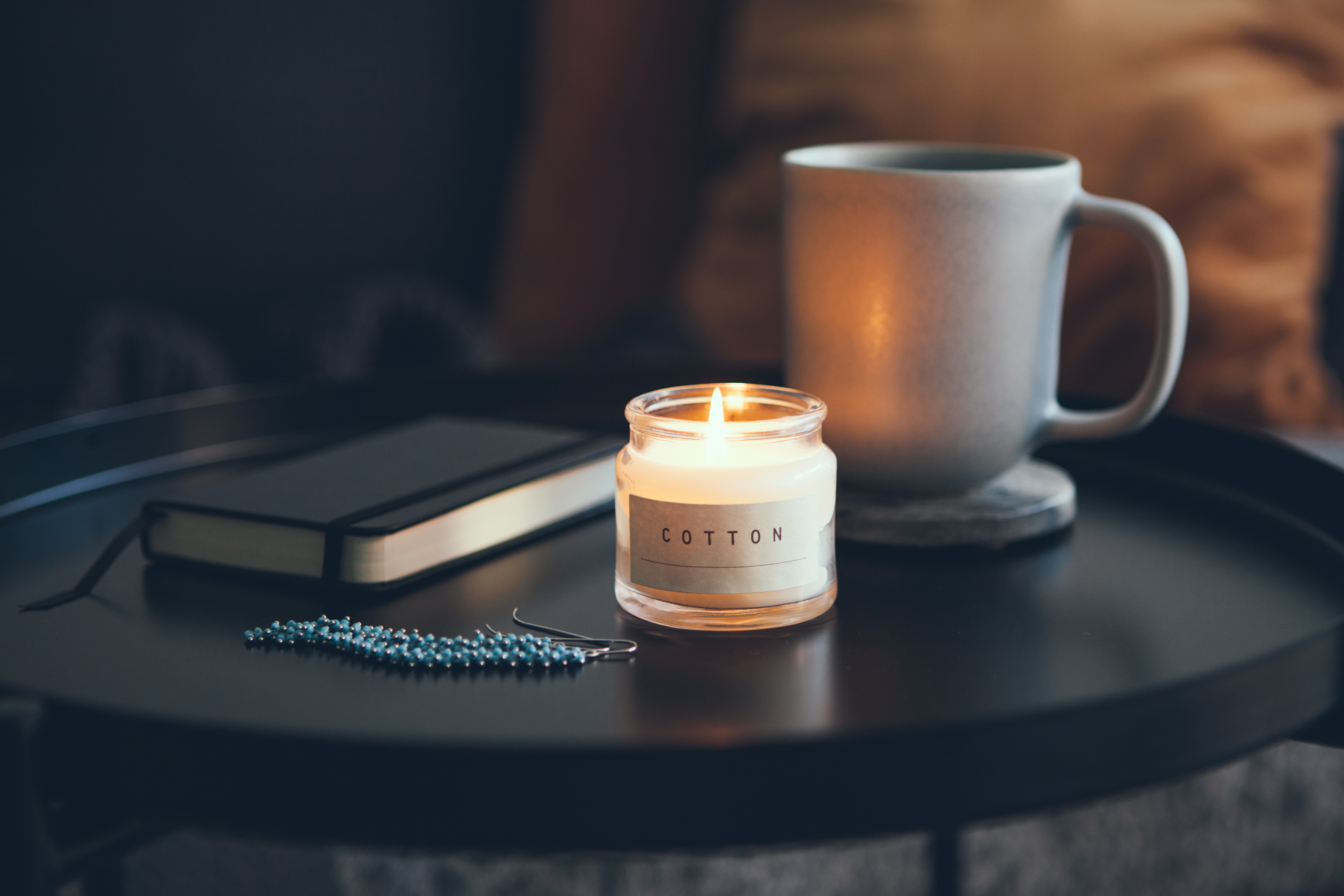 Cozy interior details. Little round table with cup of delicious tea and candle, notepad and beautiful blue color and silver earrings. Business woman resting after busy day. Selective focus.