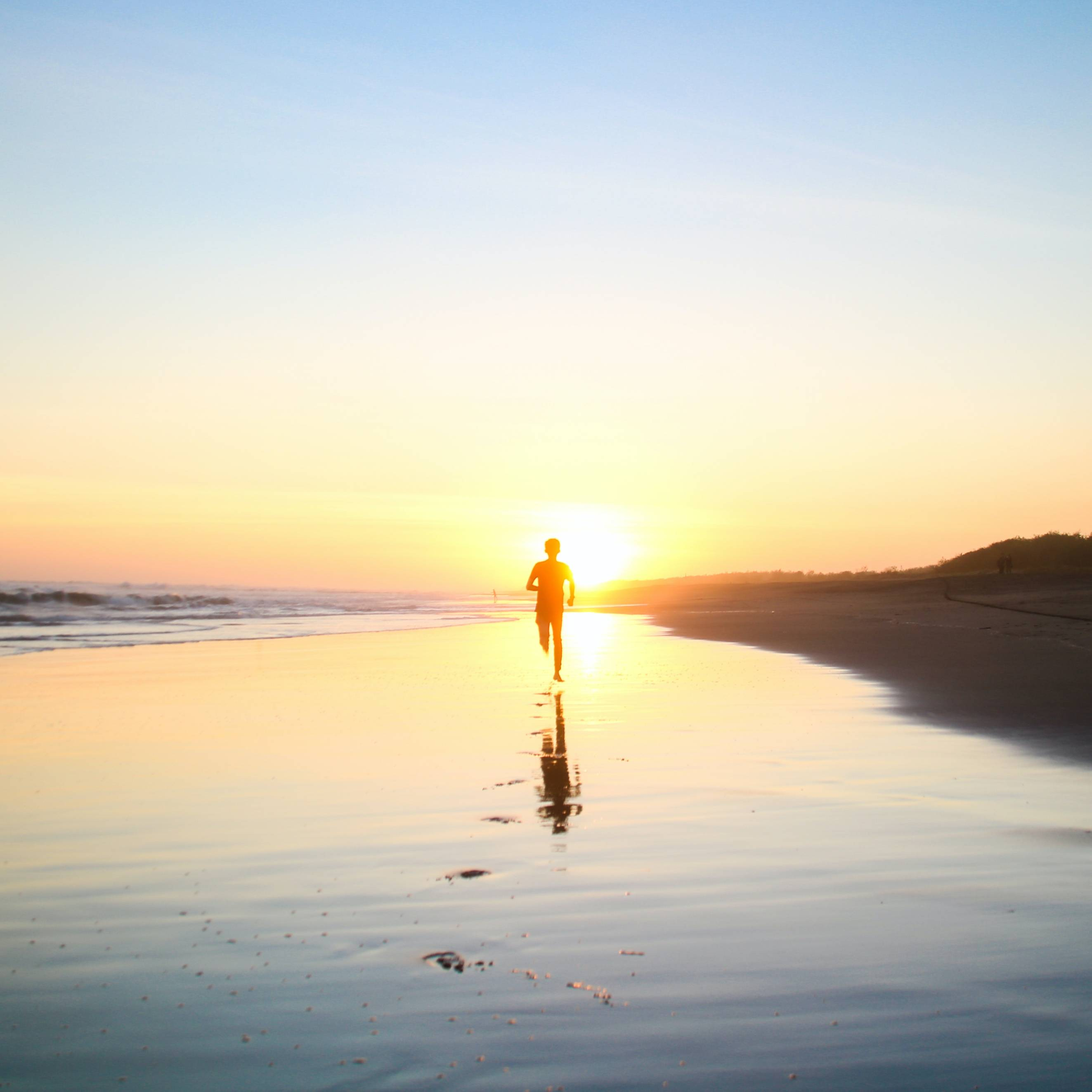 Man running as the sun rises, representing action in life