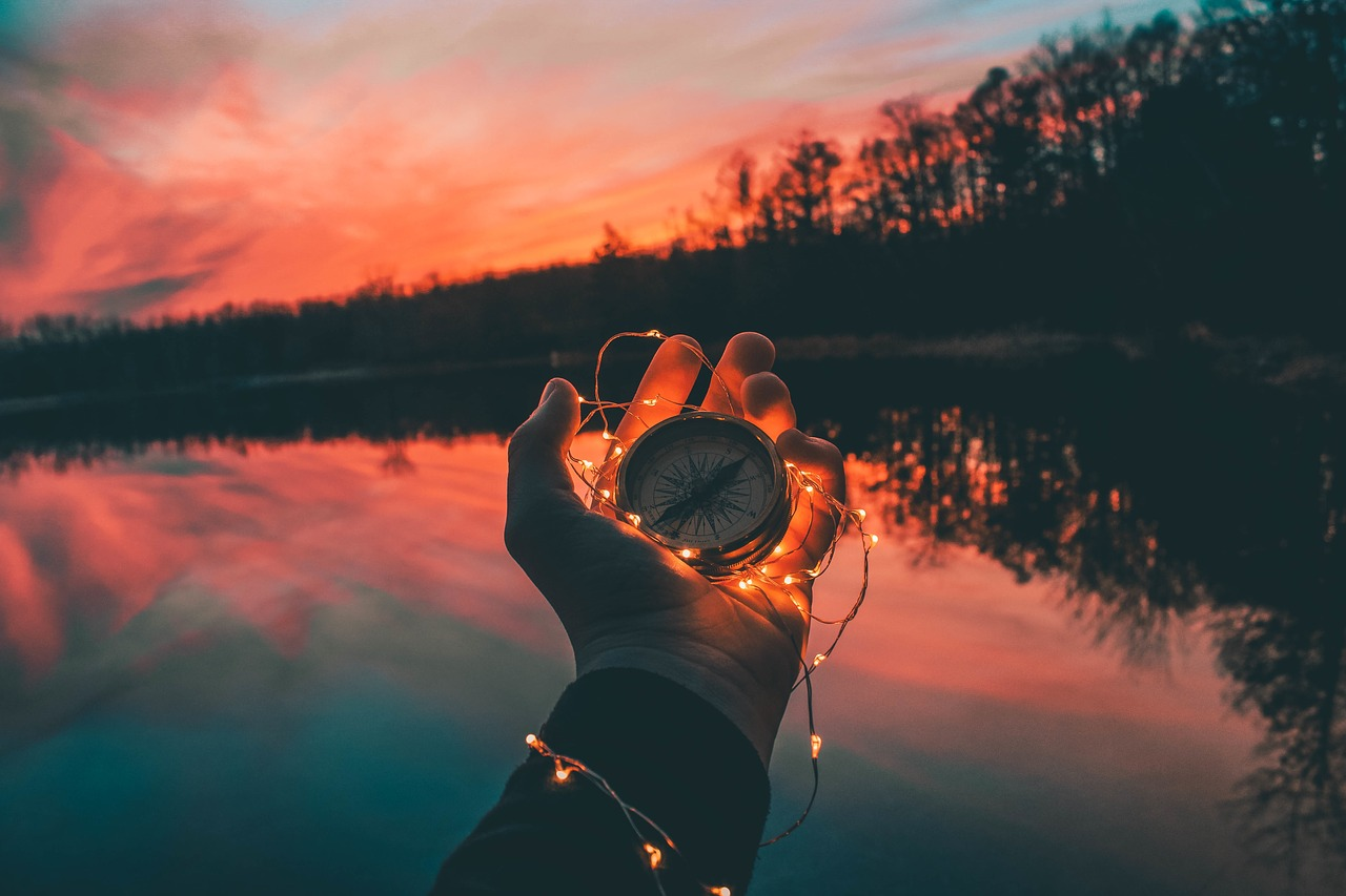 Hand holding a compass with string lights entangled