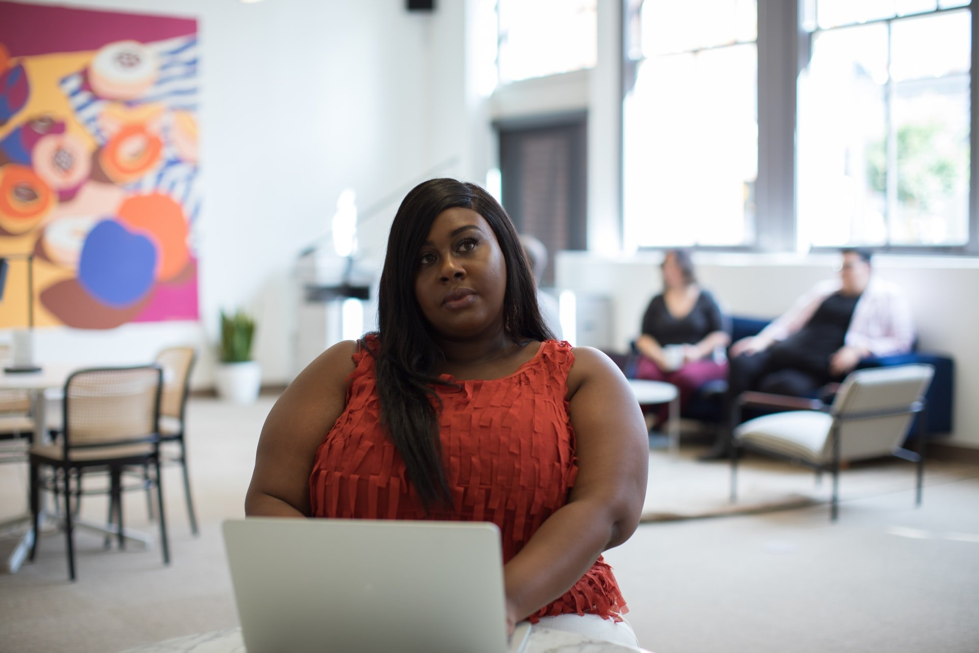 10 Ways Freelance Writers can Fight Imposter Syndrome Featured image: young black woman sitting in front of a laptop pondering something.