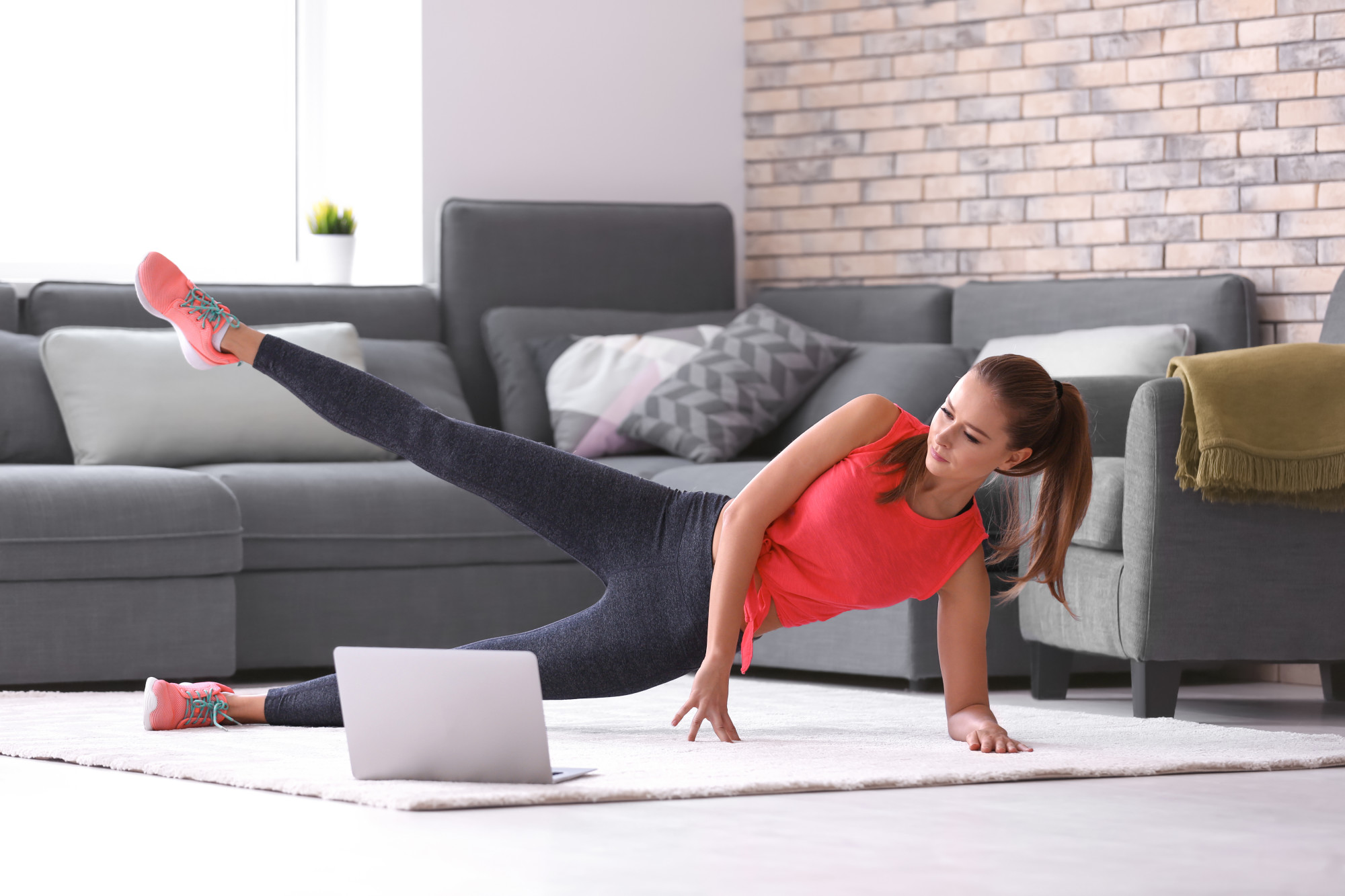 young woman doing exercises at home during quarantine