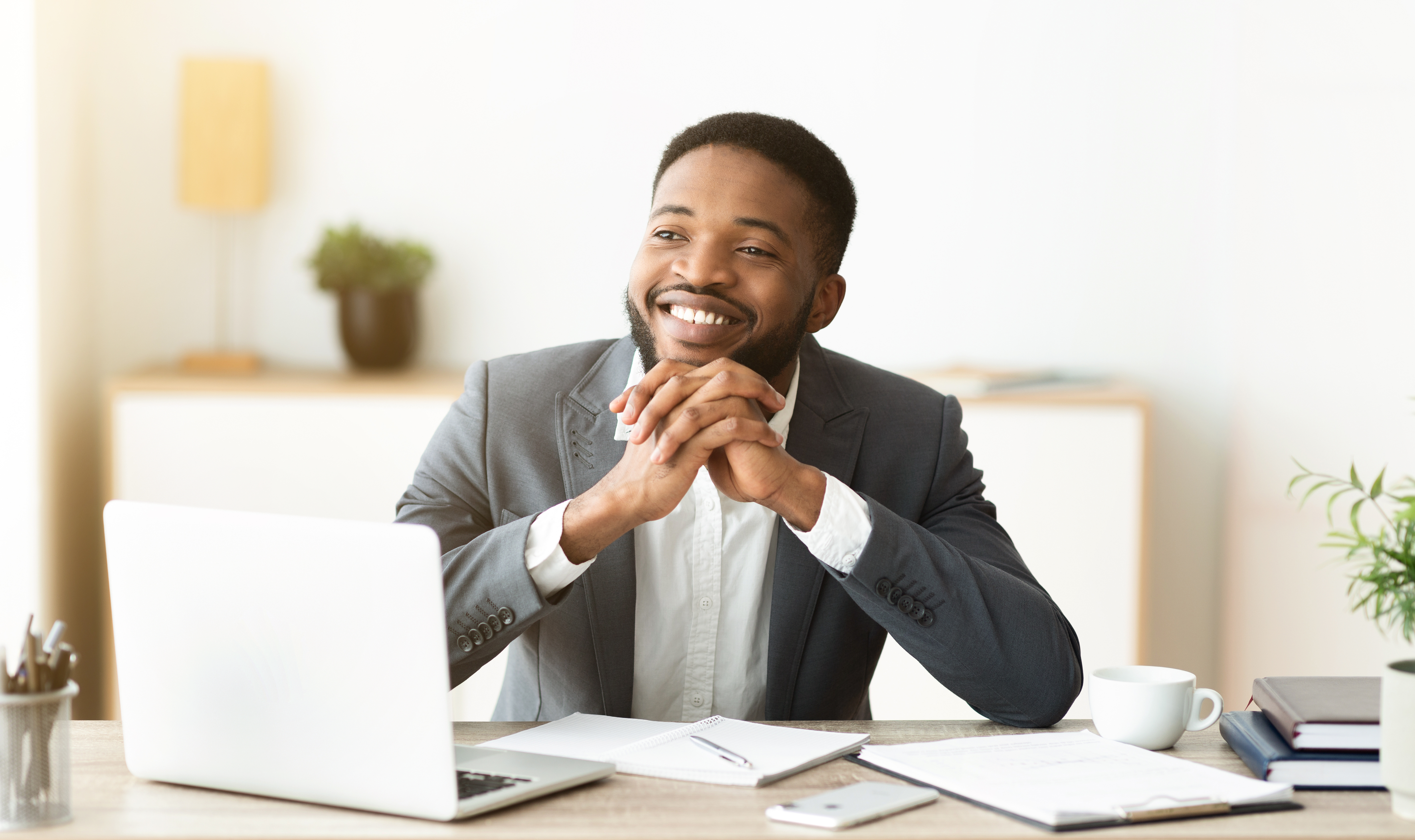 Dreamy african american businessman satisfied by results of his company, sitting at workplace in office