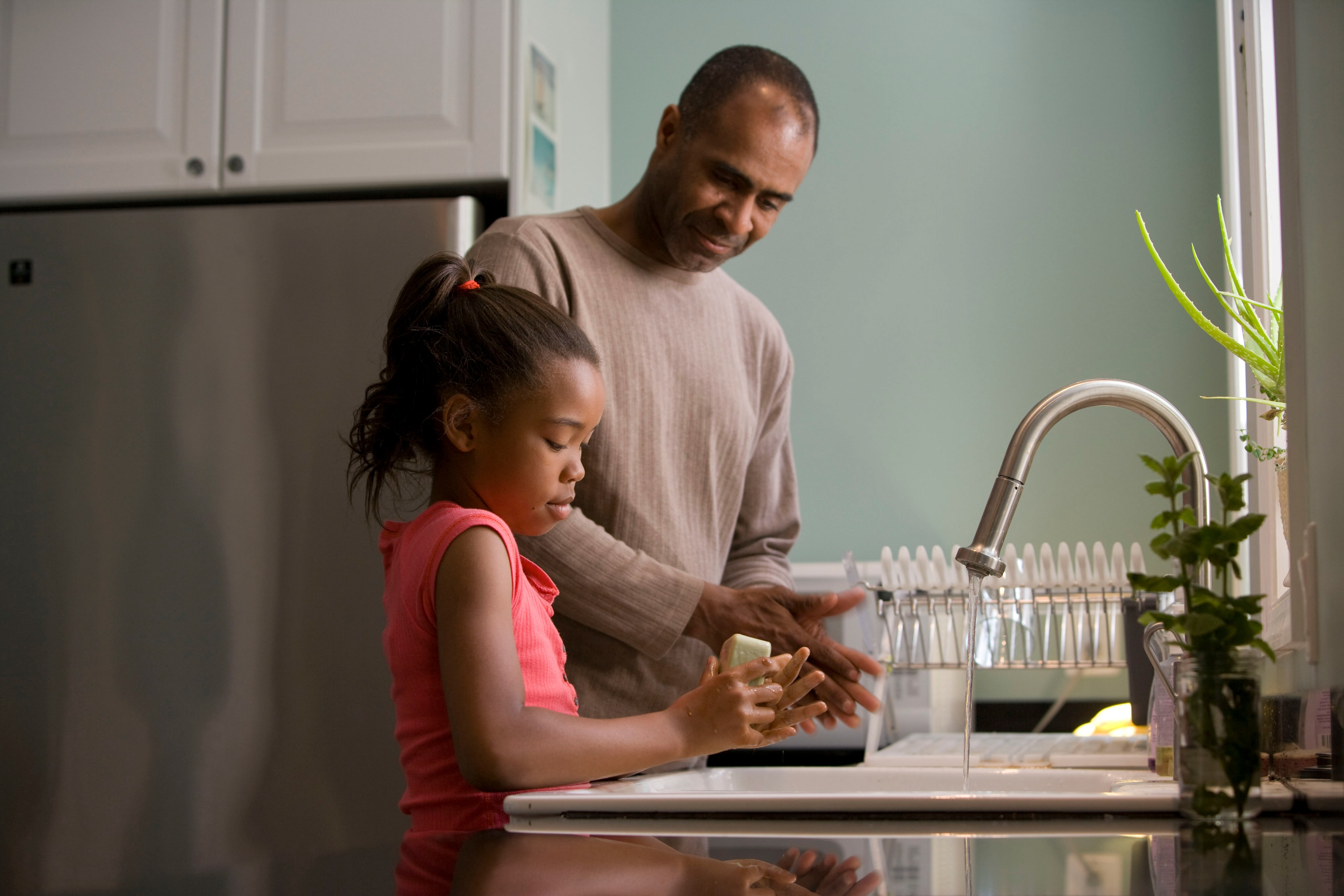 dark skinned man and young girl standing at kitchen counter top talking