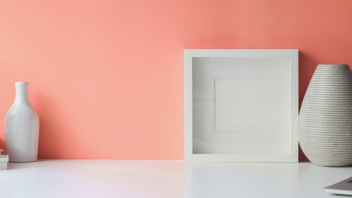 flower vase and frame in table with pink background