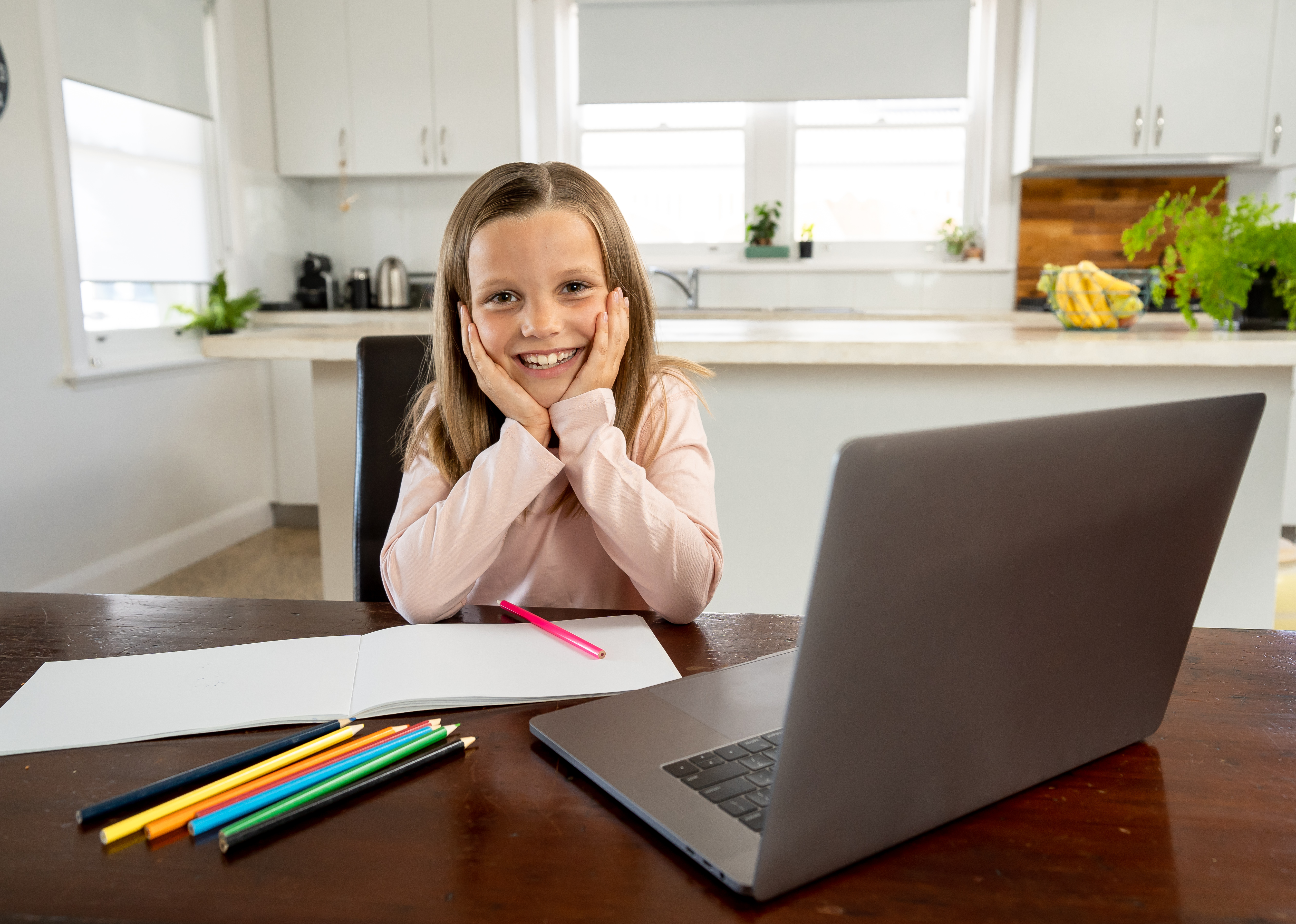 Coronavirus Outbreak. Lockdown and school closures. Schoolgirl watching online education class, happy talking with teacher on the internet at home. COVID-19 pandemic forces children online learning.