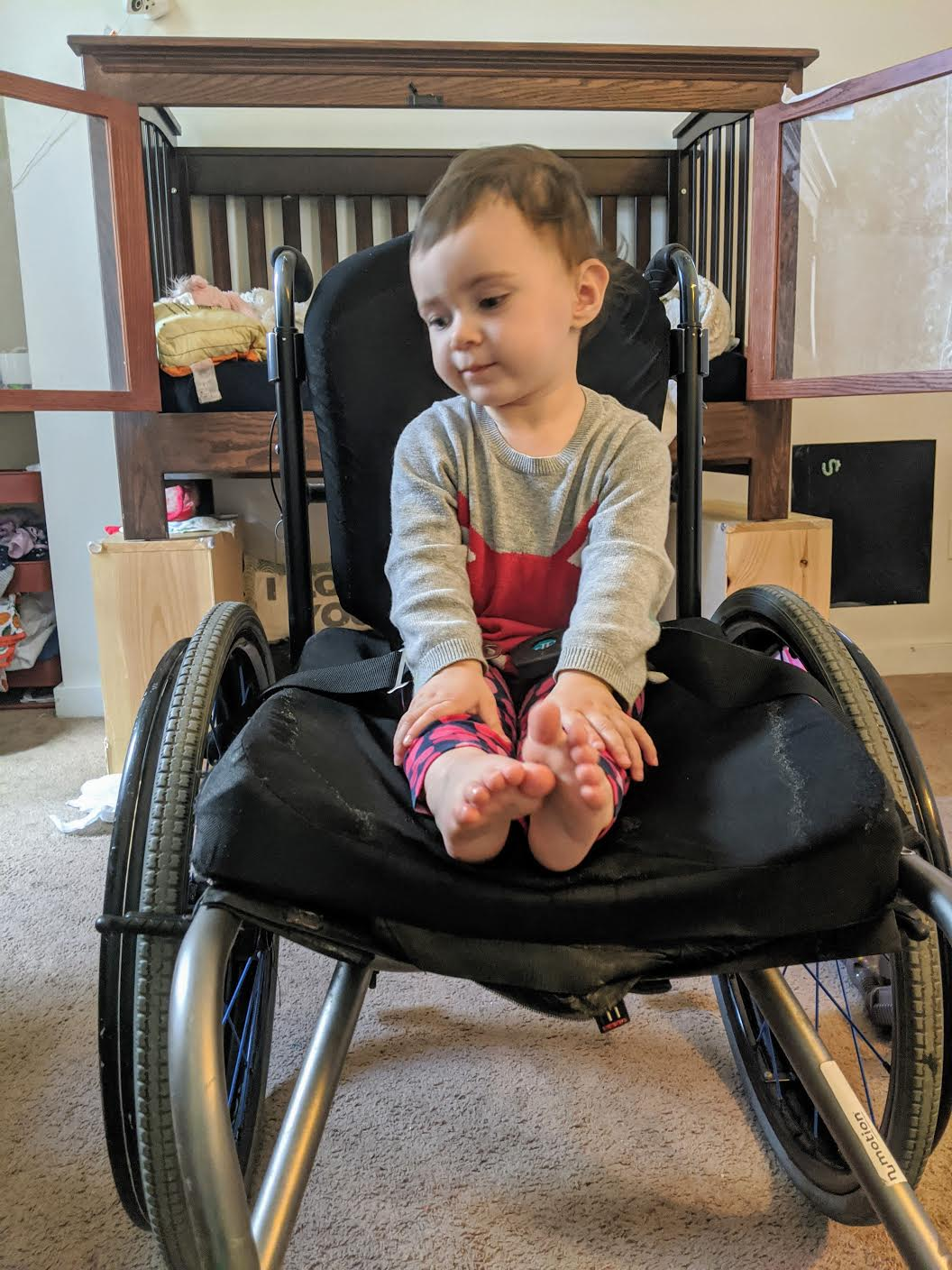 [Image Description: A young small girl sitting in a large wheelchair]