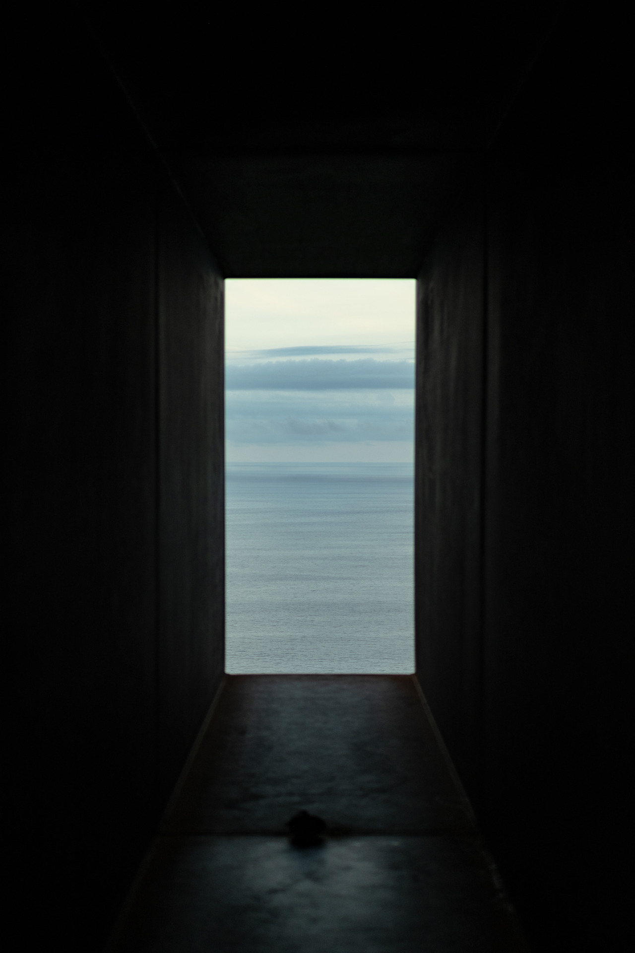 A view of the blue ocean is framed by a dark tunnel