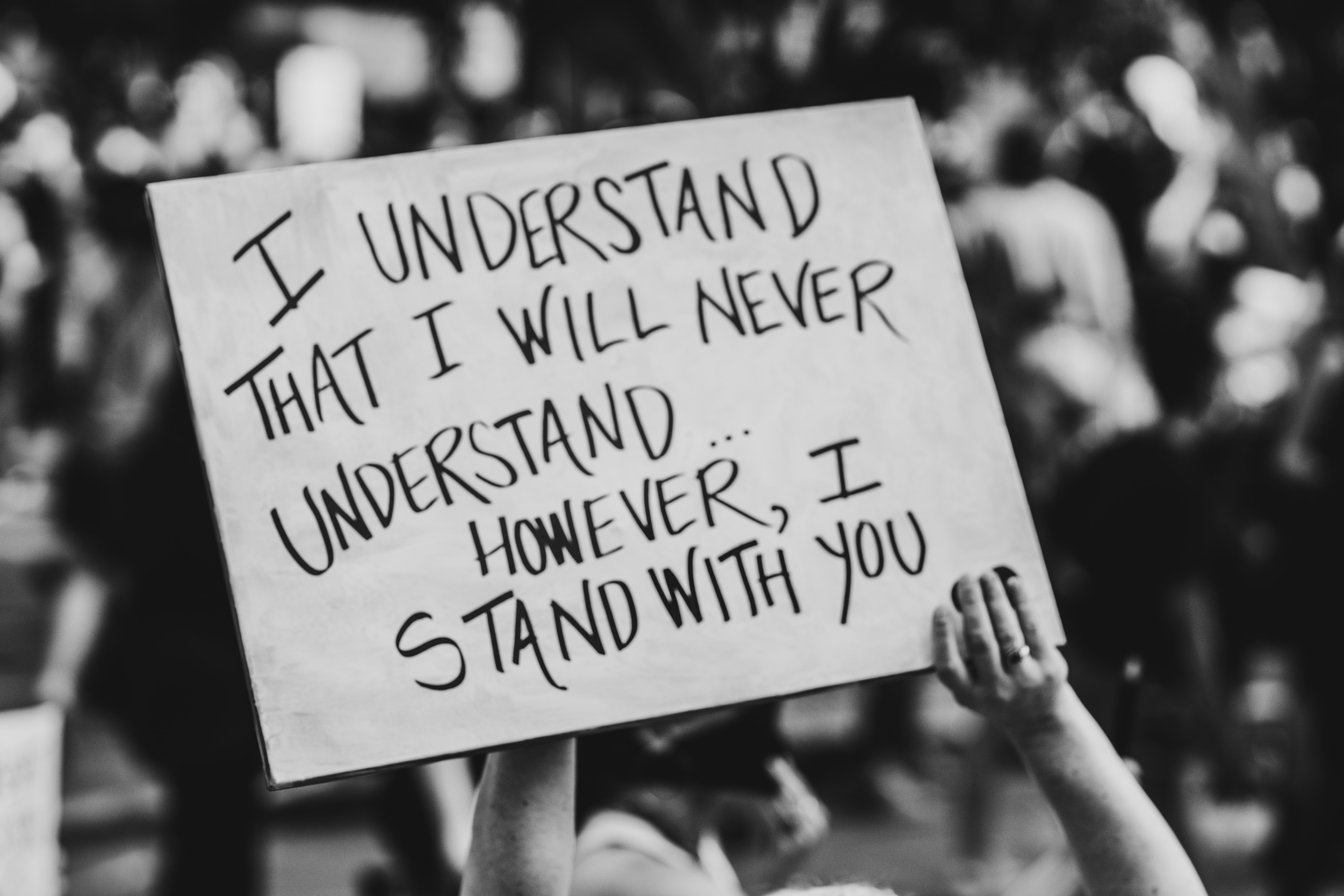 """A placard that reads """"I understand That I will never understand... However, I will stand with you"""""""