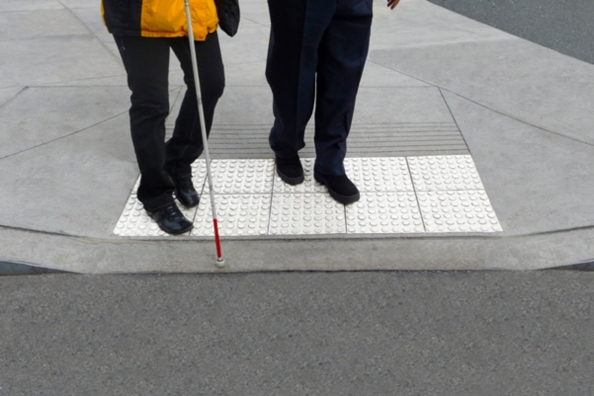 [Image Description: A picture of two people's legs. They are standing together at a crosswalk. One of these individuals is holding a white cane.]