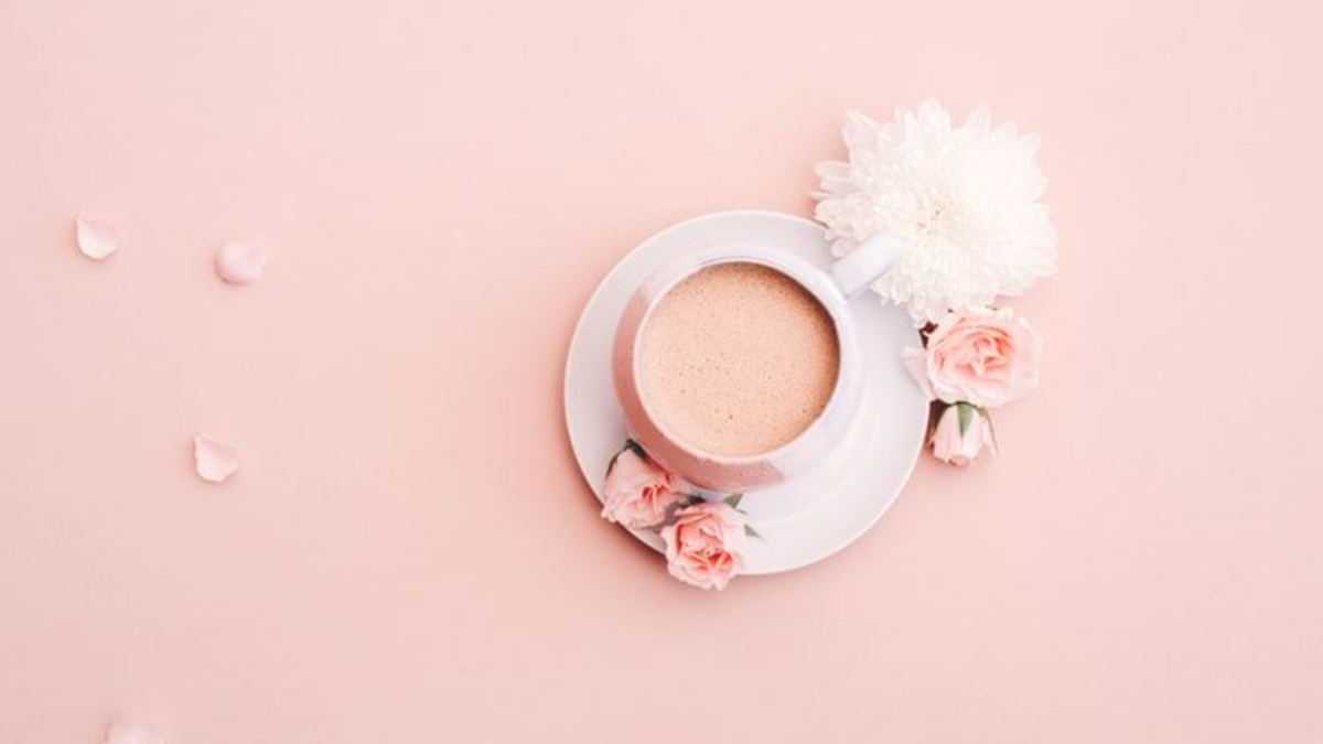 coffee, petals and small flower on pink table