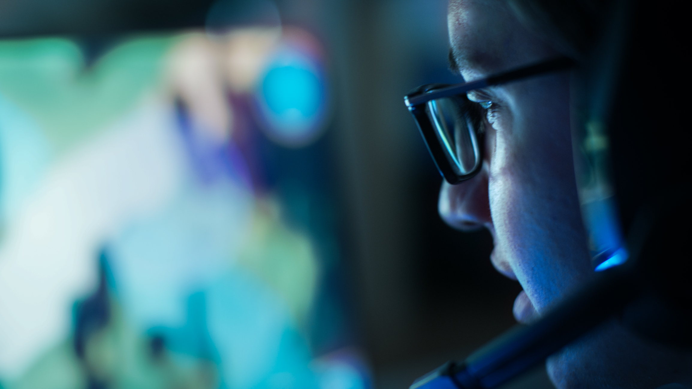 Close-up Shot of Professional Gamer Plays in MMORPG/ Strategy Video Game on His Computer. He's Participating in Online Cyber Games Tournament, Plays at Home, or in Internet Cafe. He Wears Glasses and Gaming Headsets.