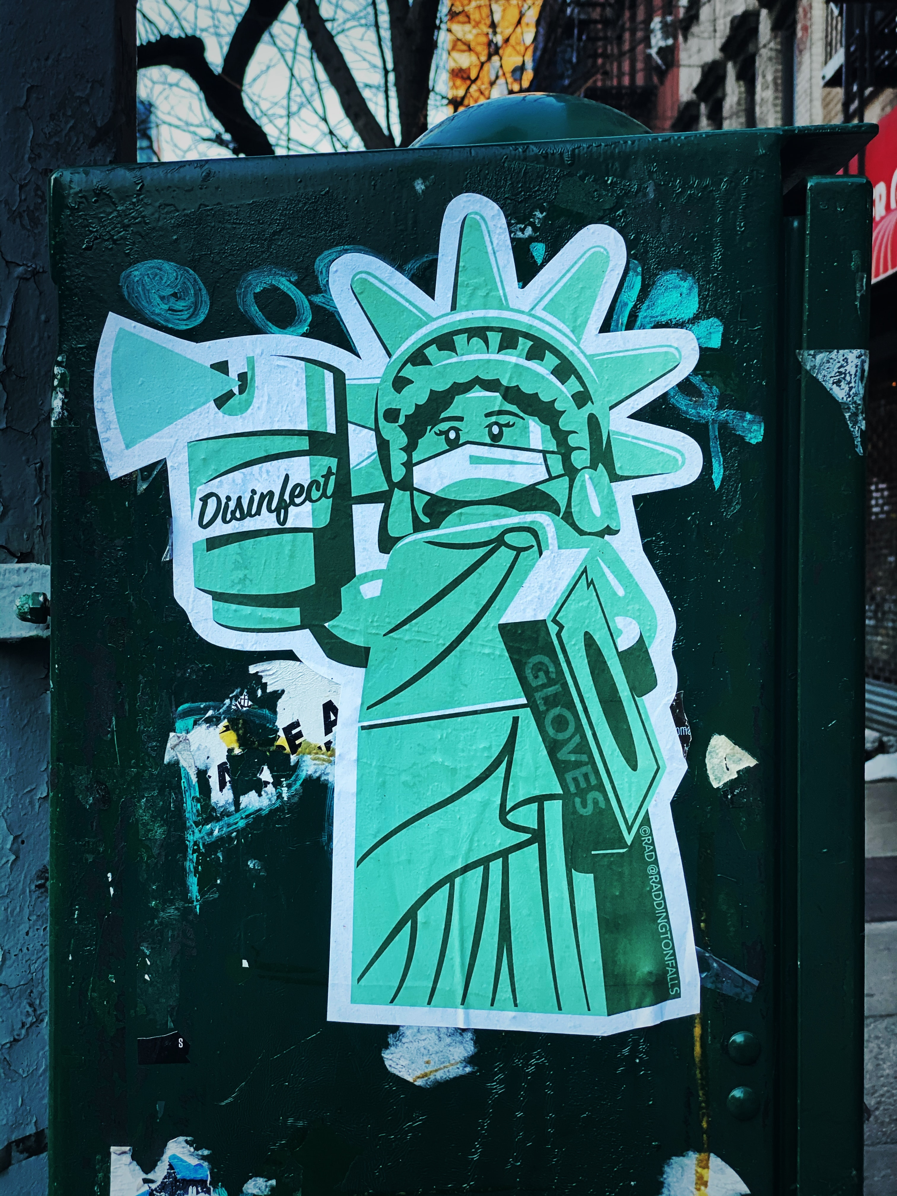 Cartoon of Statue of Liberty wearing mask and holding disinfectant spray and a box of gloves