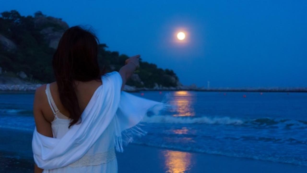 back view beautiful asian woman point finger to full moon over the seascape and mountain with reflection on the water surface at night.
