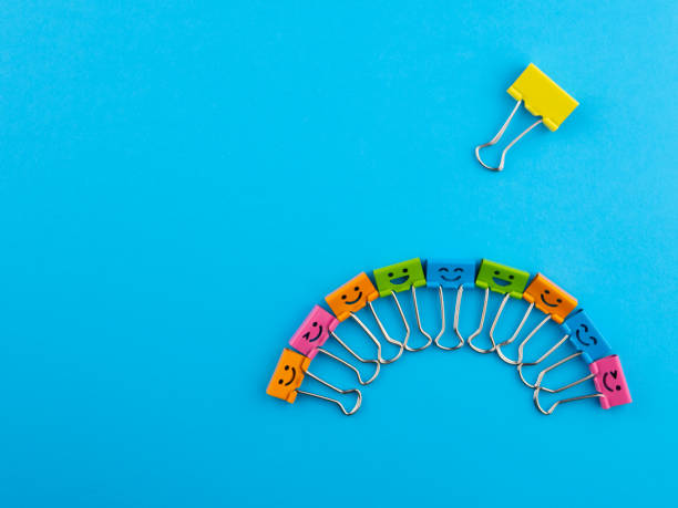 Yellow red green metal binder clip or multicolored paperclip on blue background with copyspace for text. Different, stand out of the crowd concept