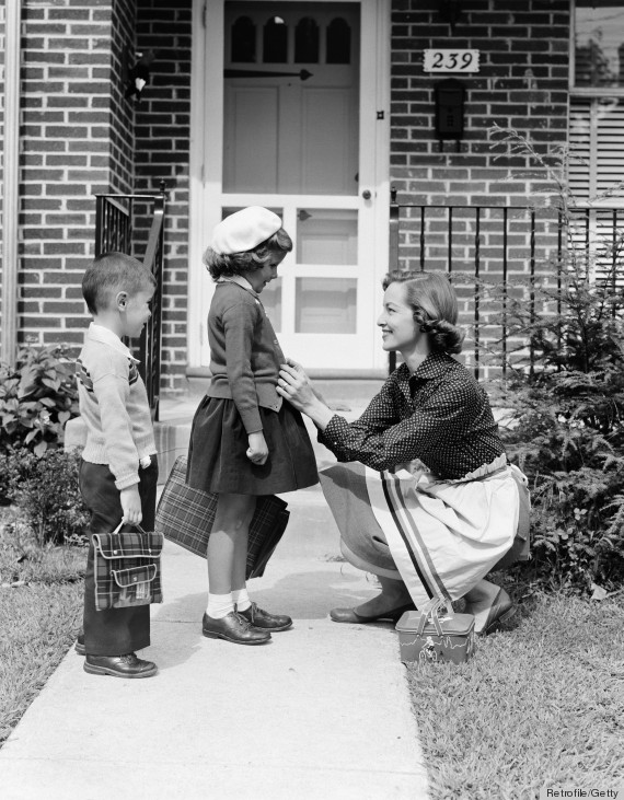 UNITED STATES - CIRCA 1950s:  Mother outside front door, buttoning sweater of daughter going off to school with her brother. (Photo by H. Armstrong Roberts/Retrofile/Getty Images)