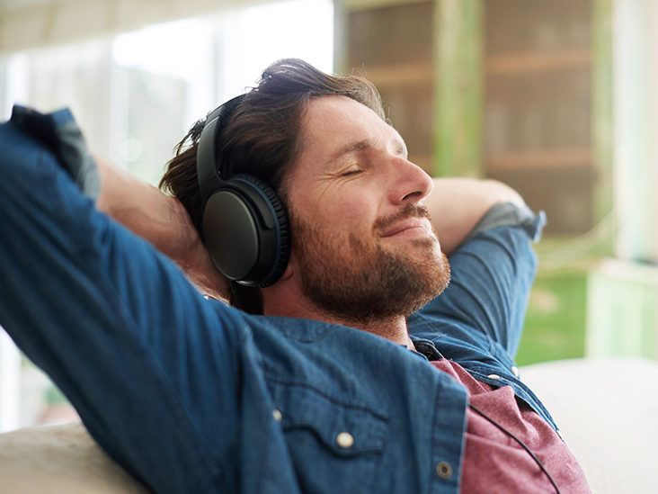Shot of a man relaxing at home with his headphones on