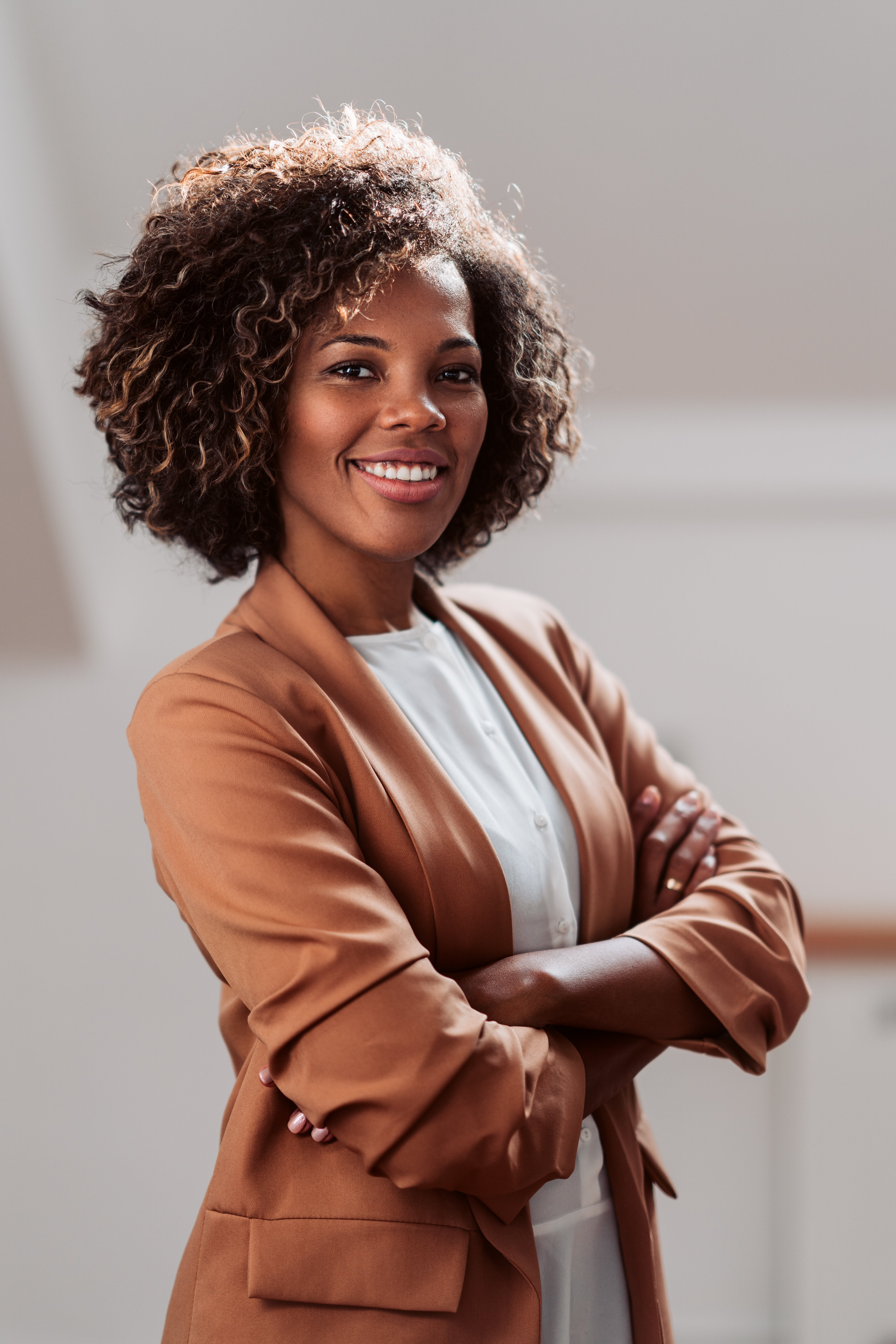Portrait of young cheerful african american businesswoman wearing brown suit smiling and looking at camera