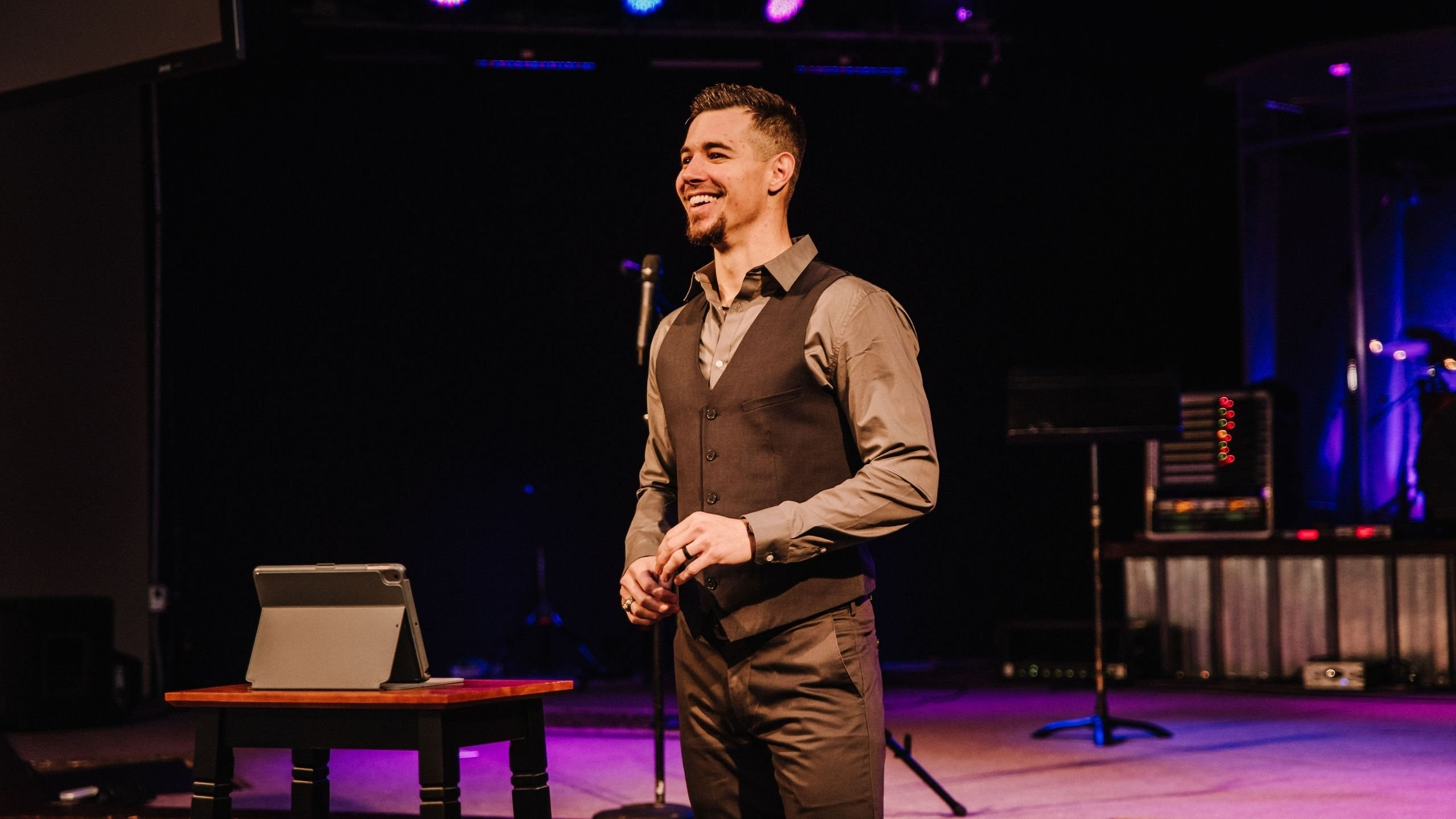 Man in a suit standing on a stage smiling