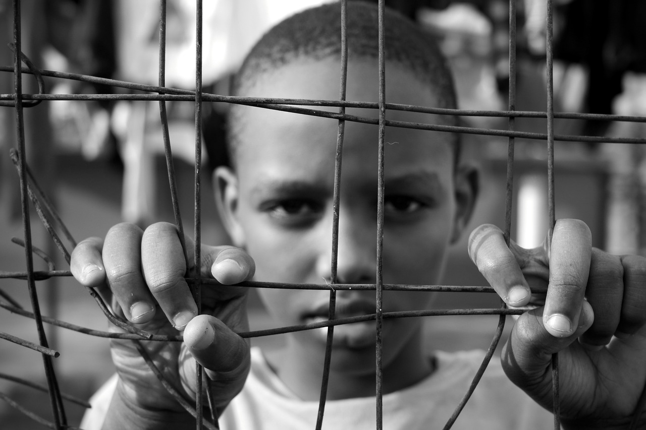 An African American teenager behind wire fencing