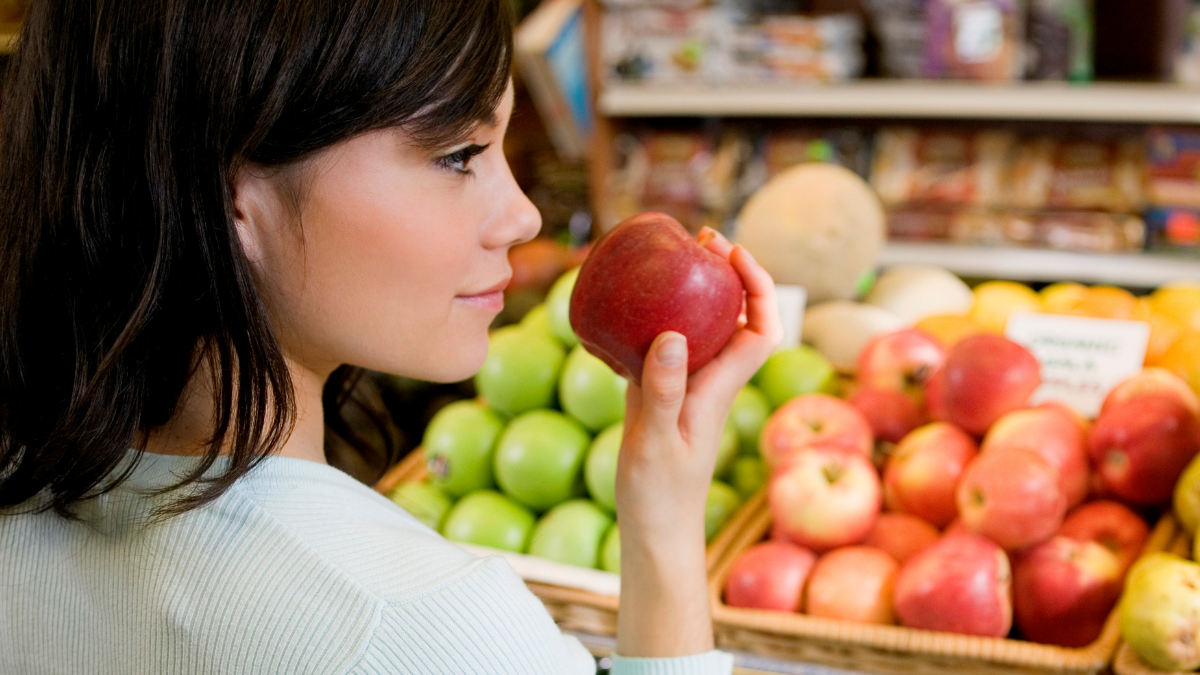 woman grocery shopping for apples