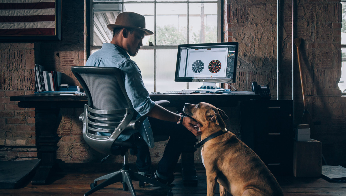 man at desk with his dog