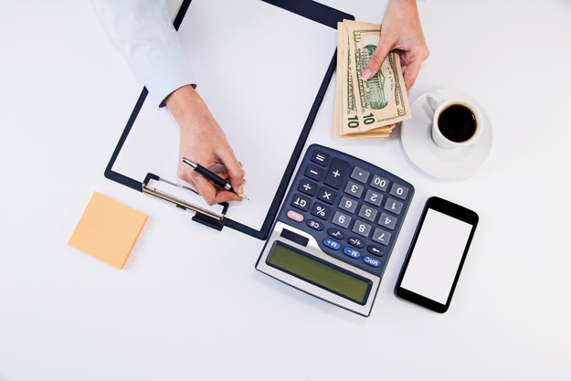 Calculating expenses. High angle of young woman calculating invoice at desk. Woman counting money at the table