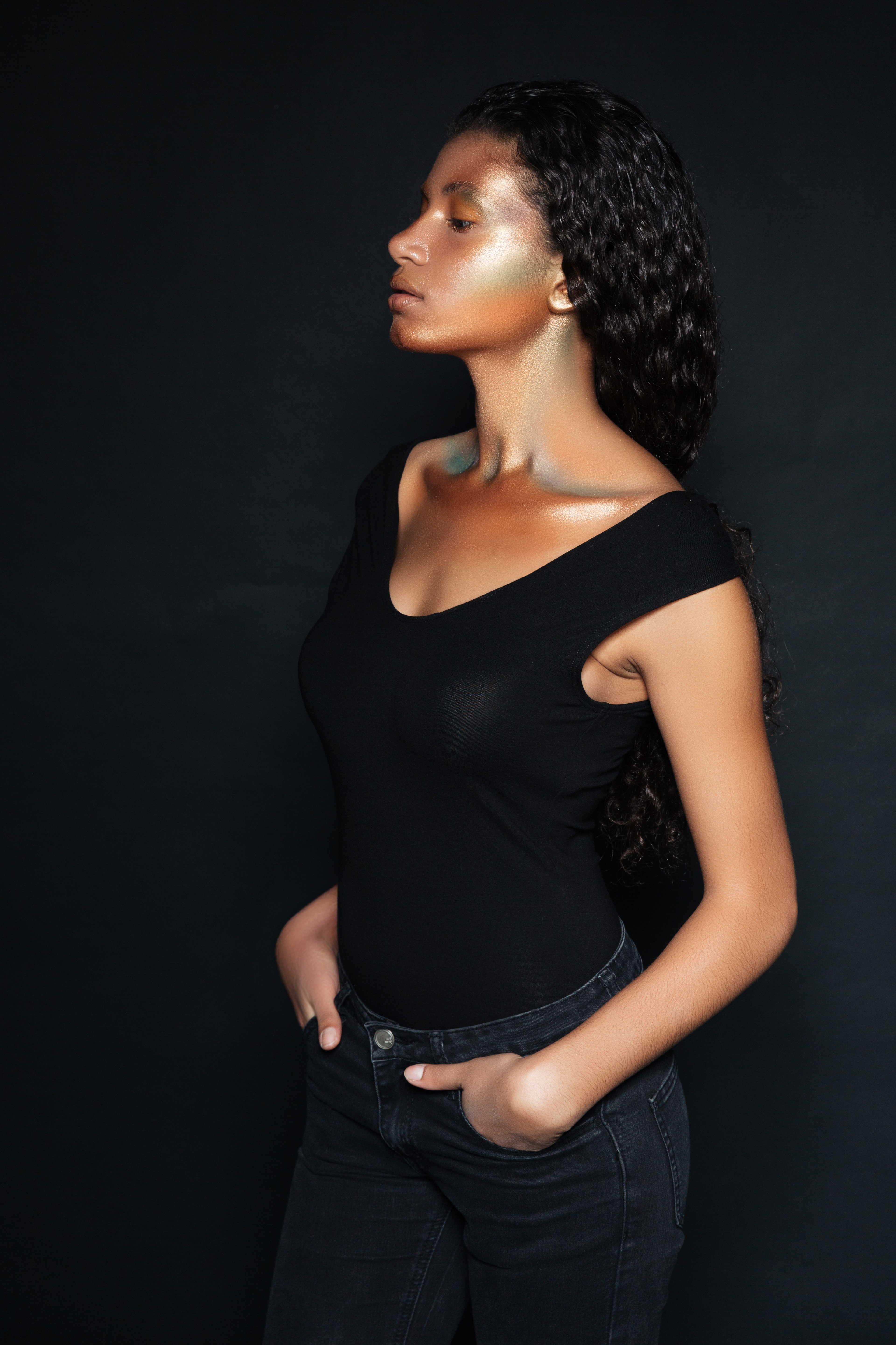Profile of beautiful african american young woman standing over black background