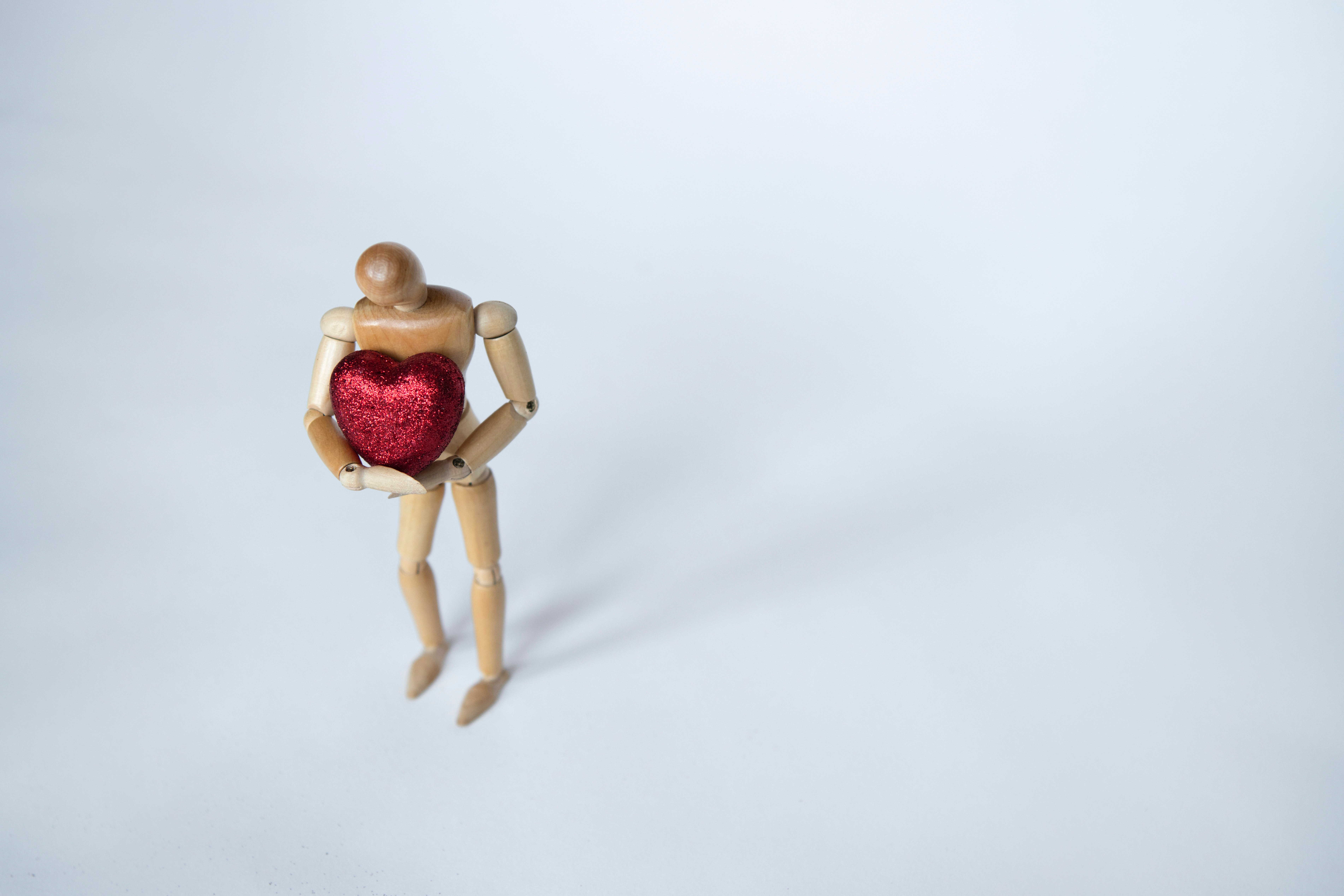 wooden figure holding a red heart