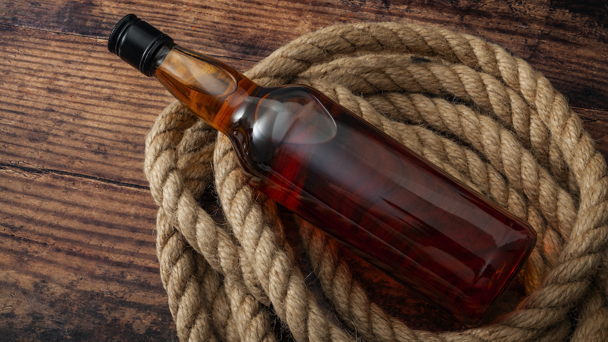 alcoholism in rural america and excessive distilled alcohol and hard liquor drinking concept theme with a bottle of scotch whiskey or brandy and rope lasso on the wooden floor in rustic dark barn