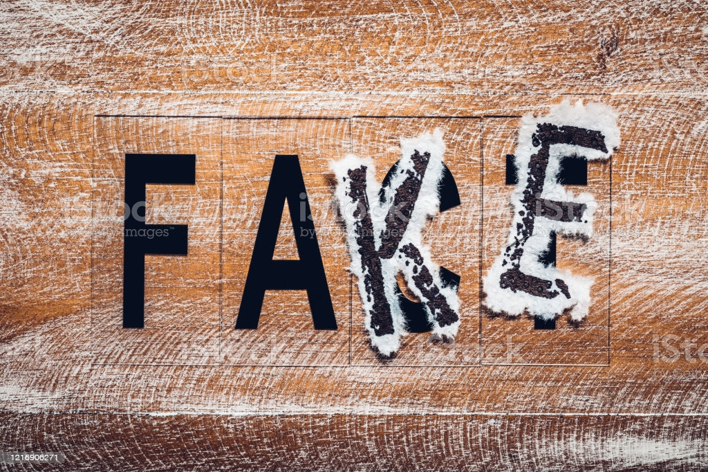 The word fake put on the word fact. The concept of false media information.