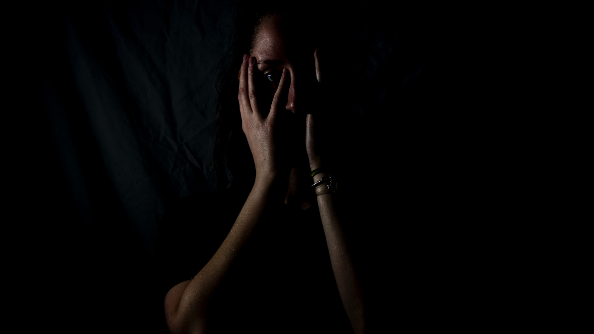 A woman lies in the dark with her face in her hands.
