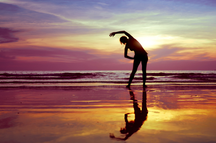 stretch before gym on the beach, silhouette of woman practicing yoga