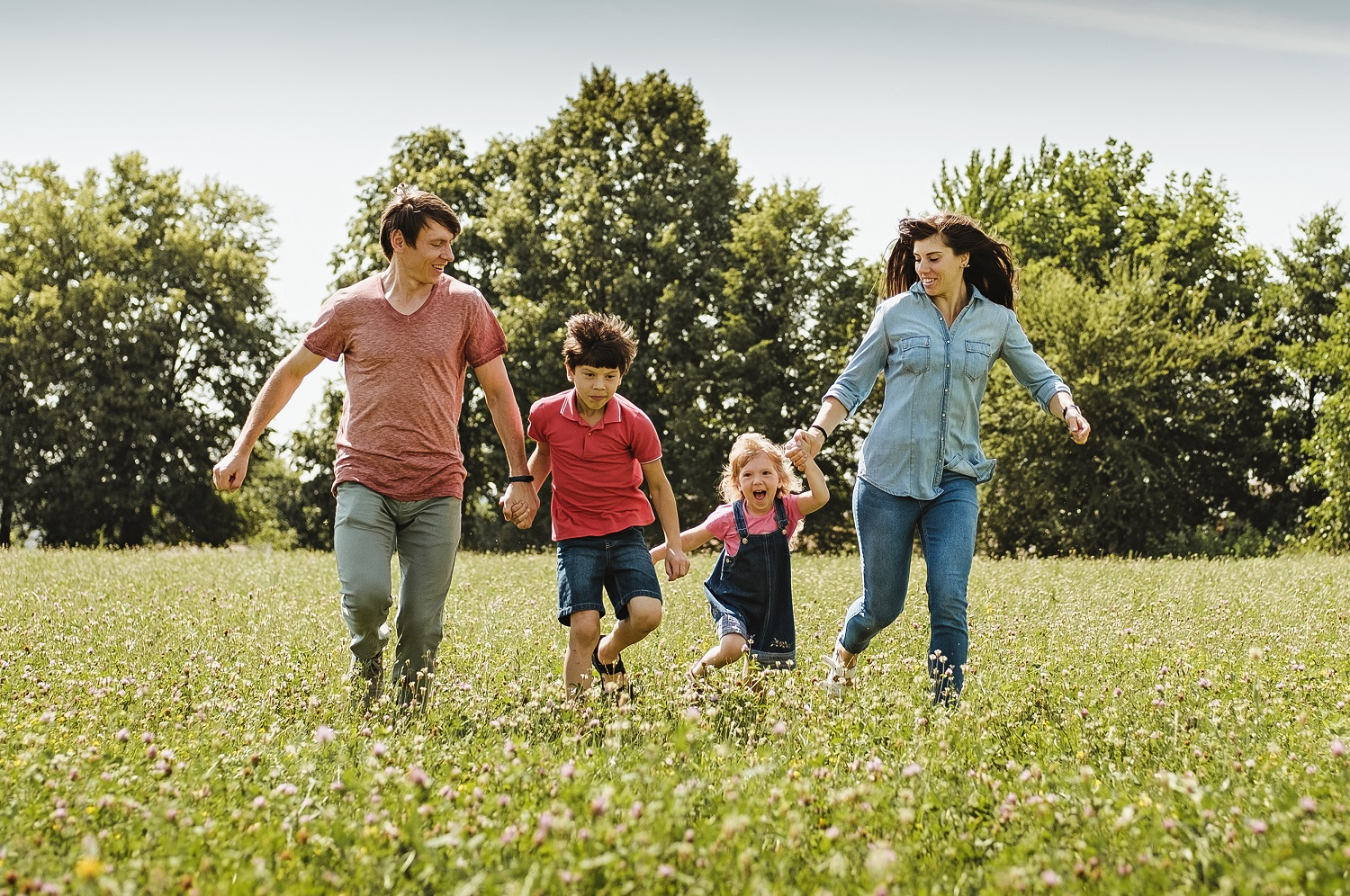 Young family with kids running hand in hand through a field or wildflowers in spring or summer approaching the camera in a healthy outdoor lifestyle concept